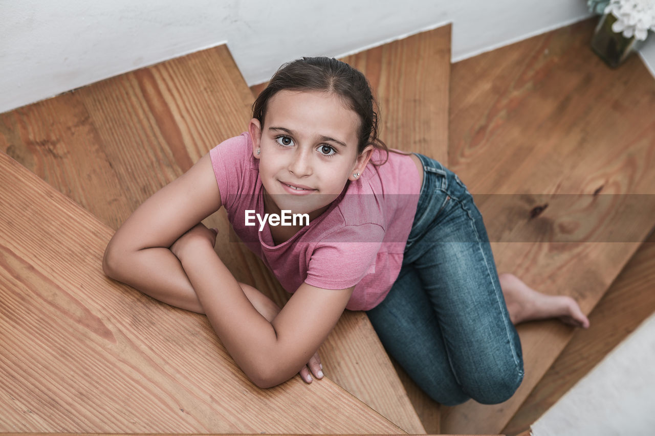 looking at camera, portrait, indoors, lifestyles, high angle view, real people, wood - material, casual clothing, flooring, leisure activity, one person, home interior, sitting, child, hardwood floor, girls, females, childhood, wood, pink color, innocence, parquet floor, hairstyle, beautiful woman, teenager