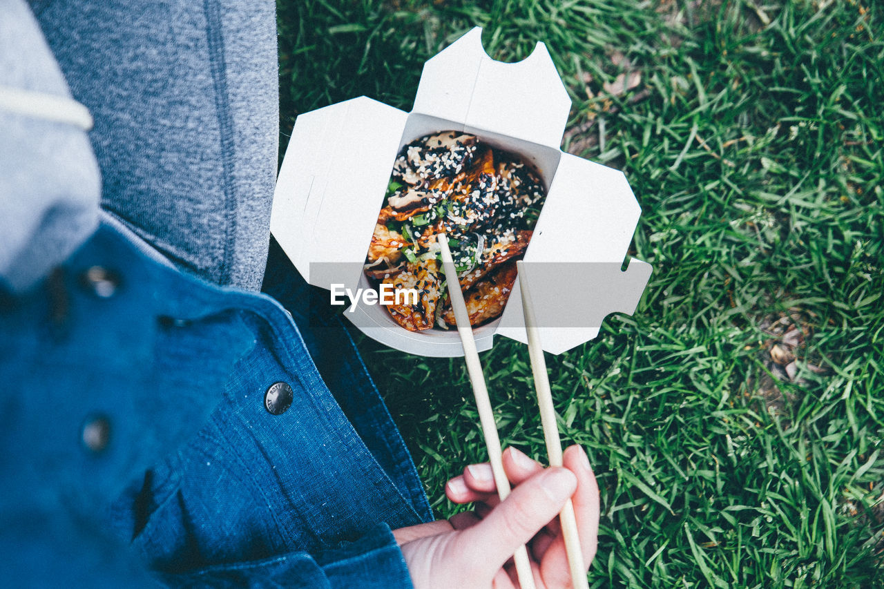 Midsection Of Person With Food On Grass