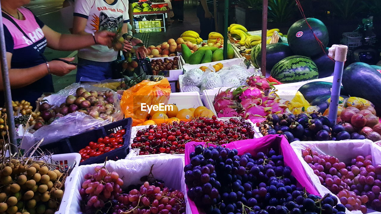 fruit, variation, food and drink, freshness, food, choice, market stall, healthy eating, market, for sale, abundance, grape, retail, day, large group of objects, arrangement, outdoors, apple - fruit, banana, real people, multi colored, peach, price tag, mango, pitaya, women