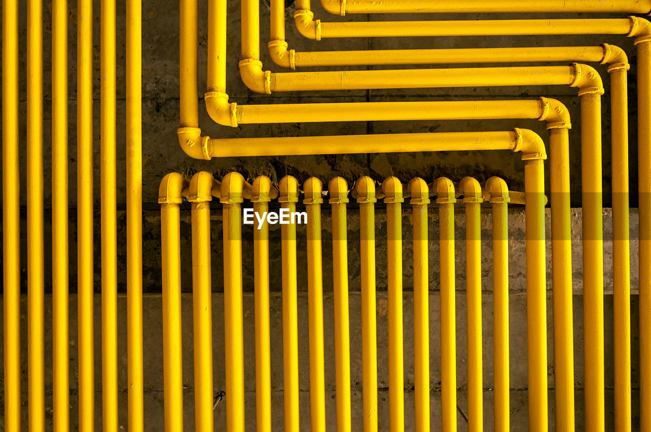 Yellow Pipes Connected Against Wall