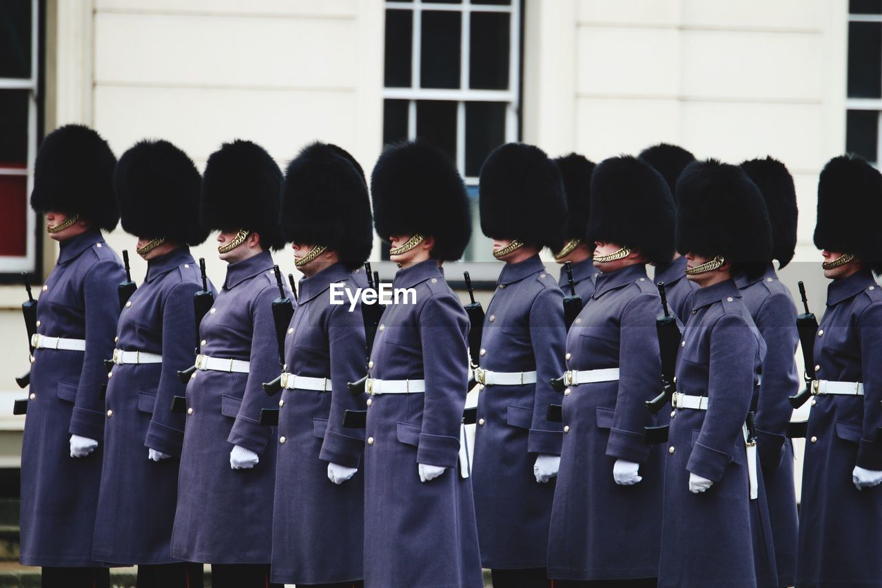Soldiers wearing blue uniform in parade against building