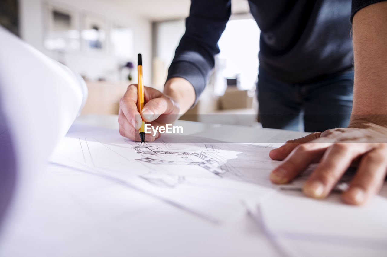 MIDSECTION OF MAN WORKING ON PAPER WITH TABLE