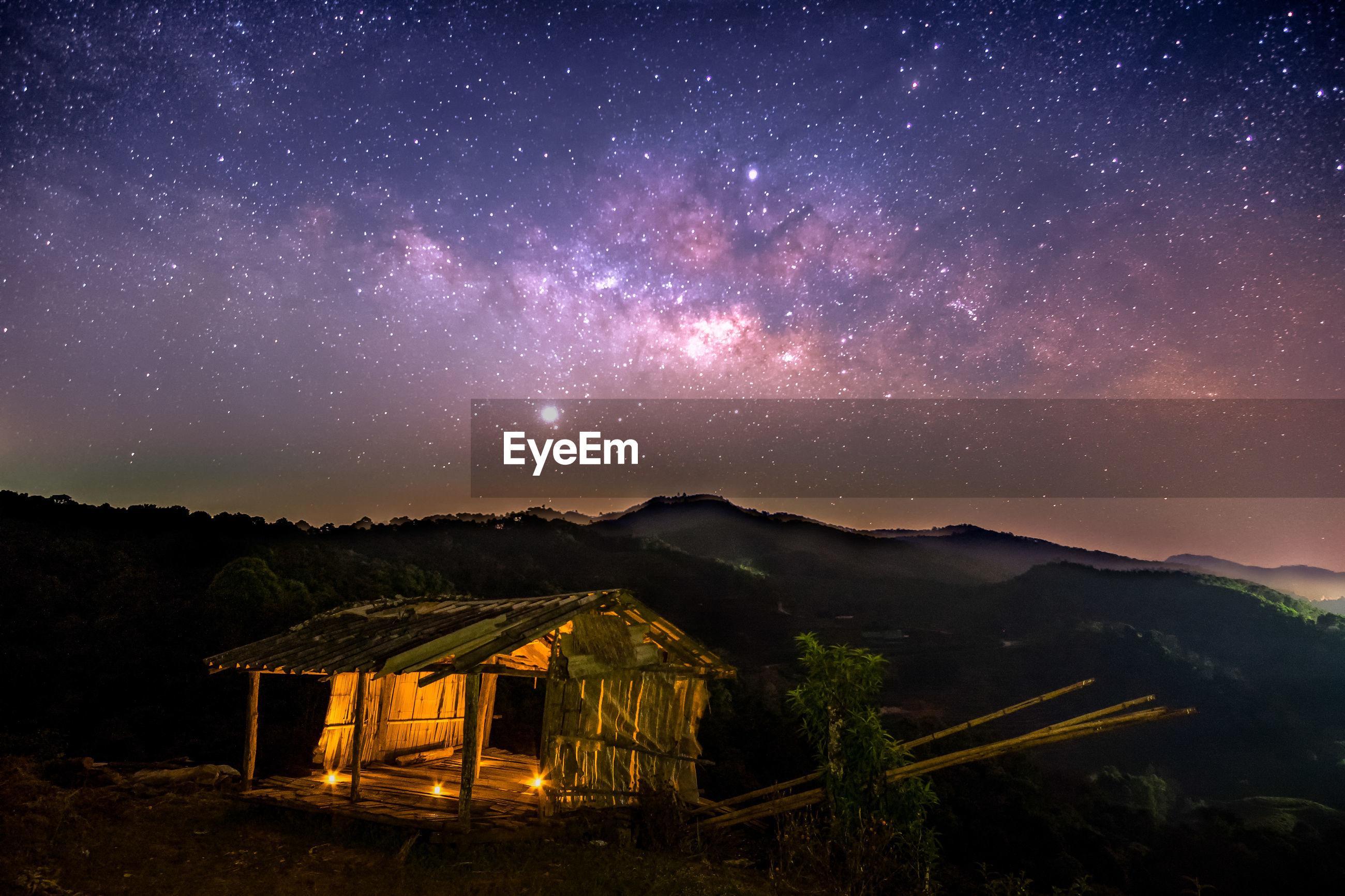 Illuminated broken house on mountain against star field sky