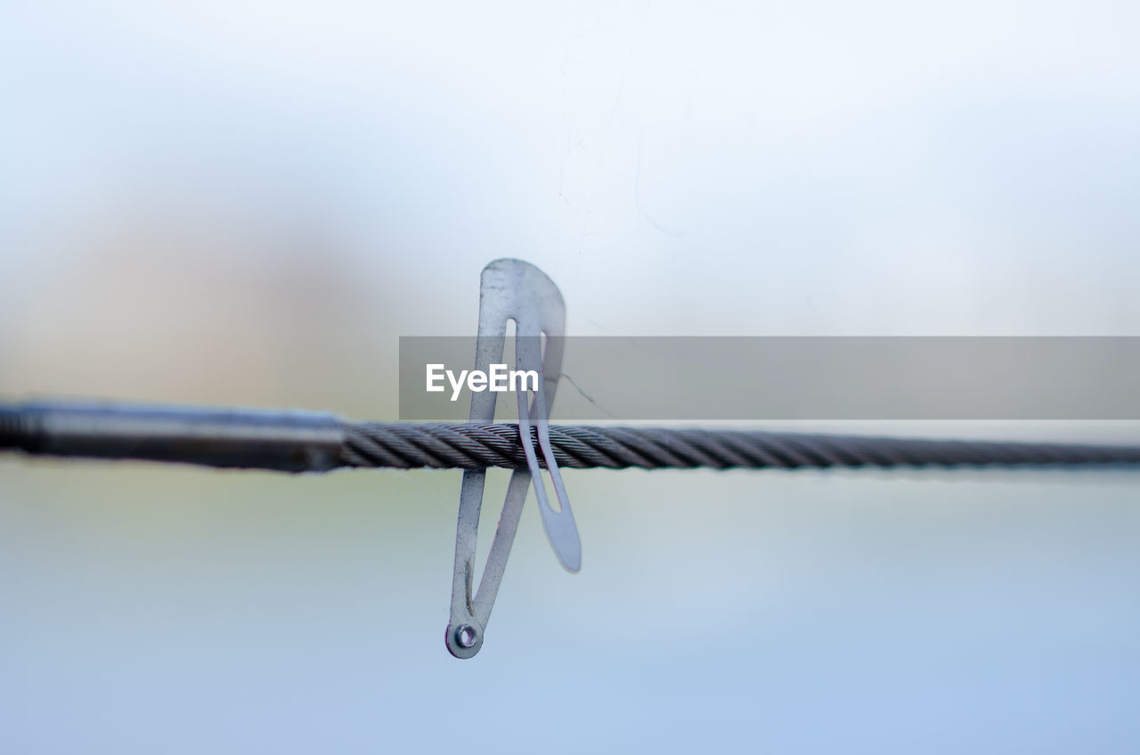 metal, close-up, no people, wire, focus on foreground, selective focus, clothesline, safety, barbed wire, protection, sharp, still life, security, day, clothespin, fence, hanging, single object, copy space, thread, steel