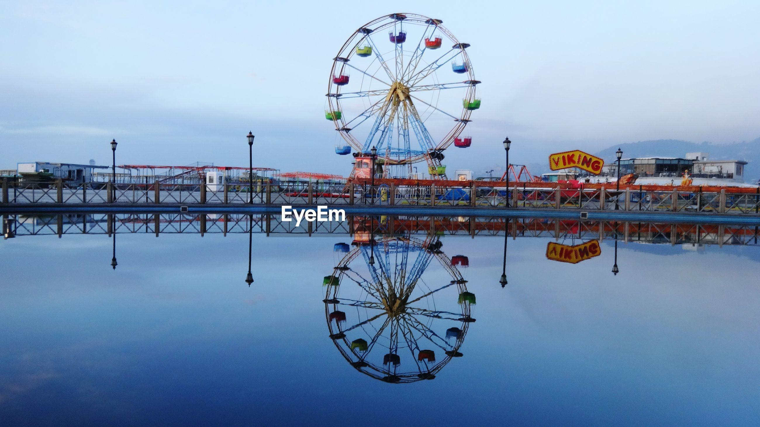 Reflection of ferris wheel in lake
