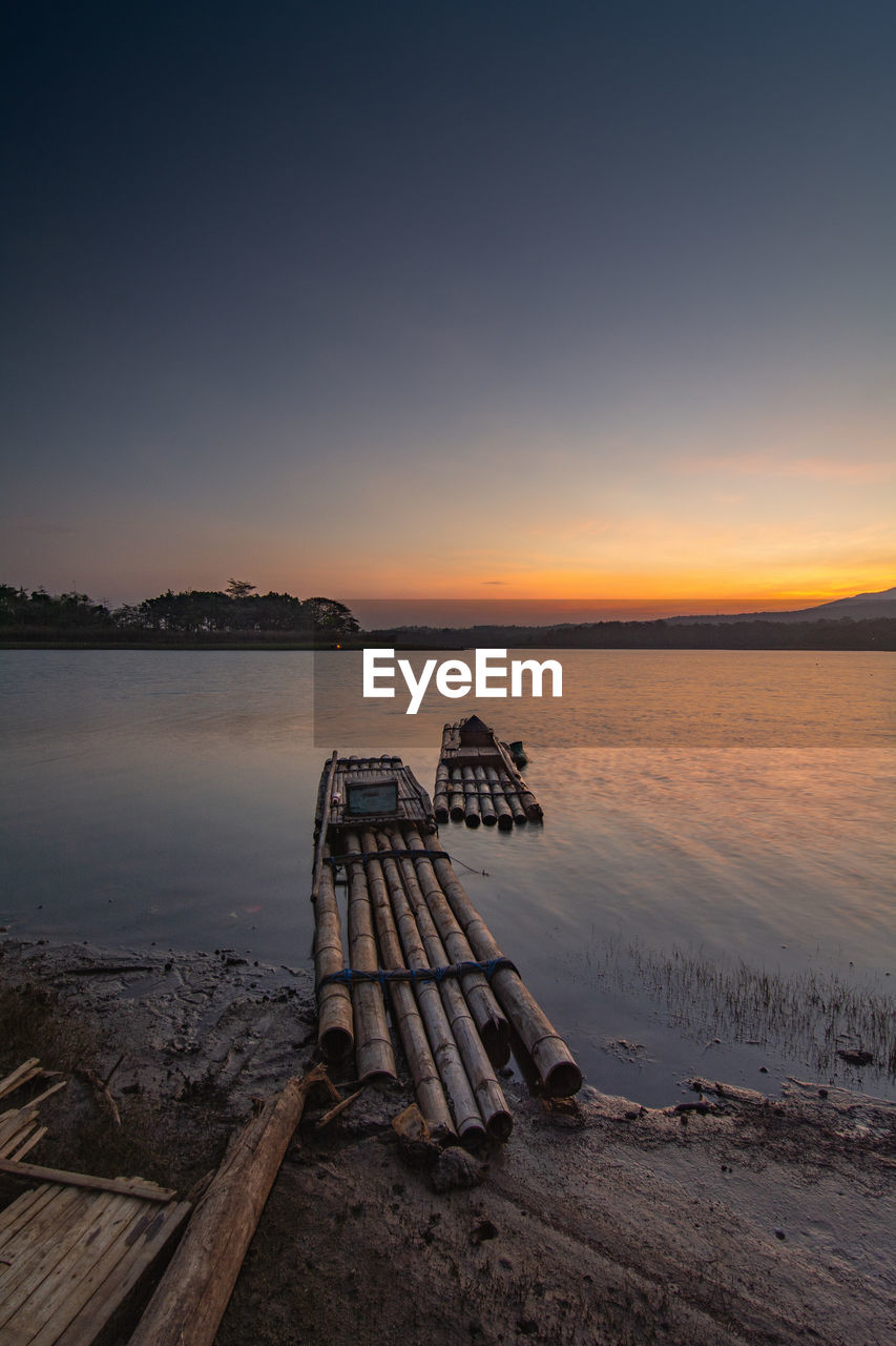 sky, water, sunset, scenics - nature, tranquility, tranquil scene, beauty in nature, idyllic, nature, non-urban scene, wood - material, no people, lake, orange color, seat, beach, copy space, land, outdoors