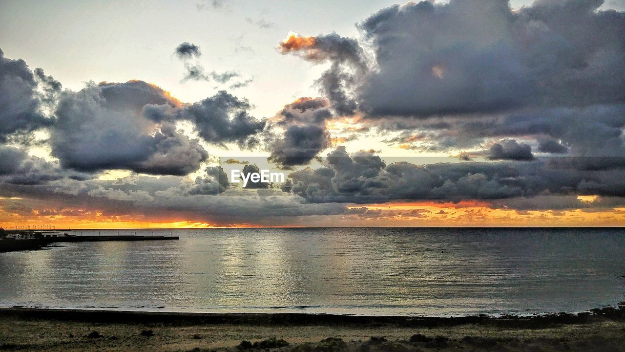 sunset, beauty in nature, sky, cloud - sky, scenics, nature, tranquil scene, tranquility, sea, water, dramatic sky, no people, outdoors, idyllic, horizon over water, silhouette, storm cloud, beach, day