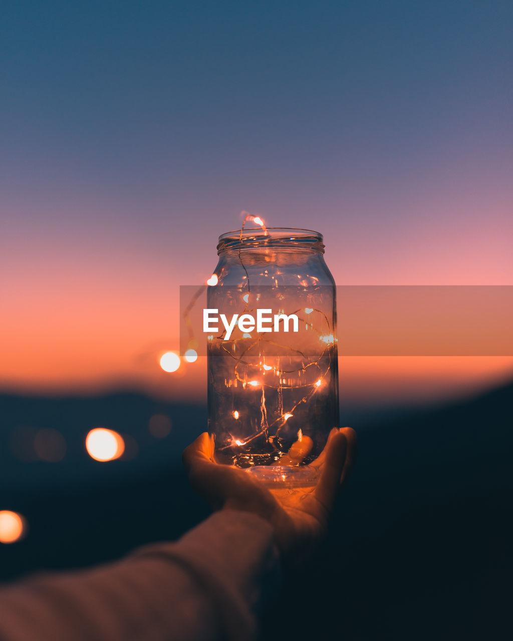 Close-Up Of Hand Holding Jar With Illuminated Lights At Sunset