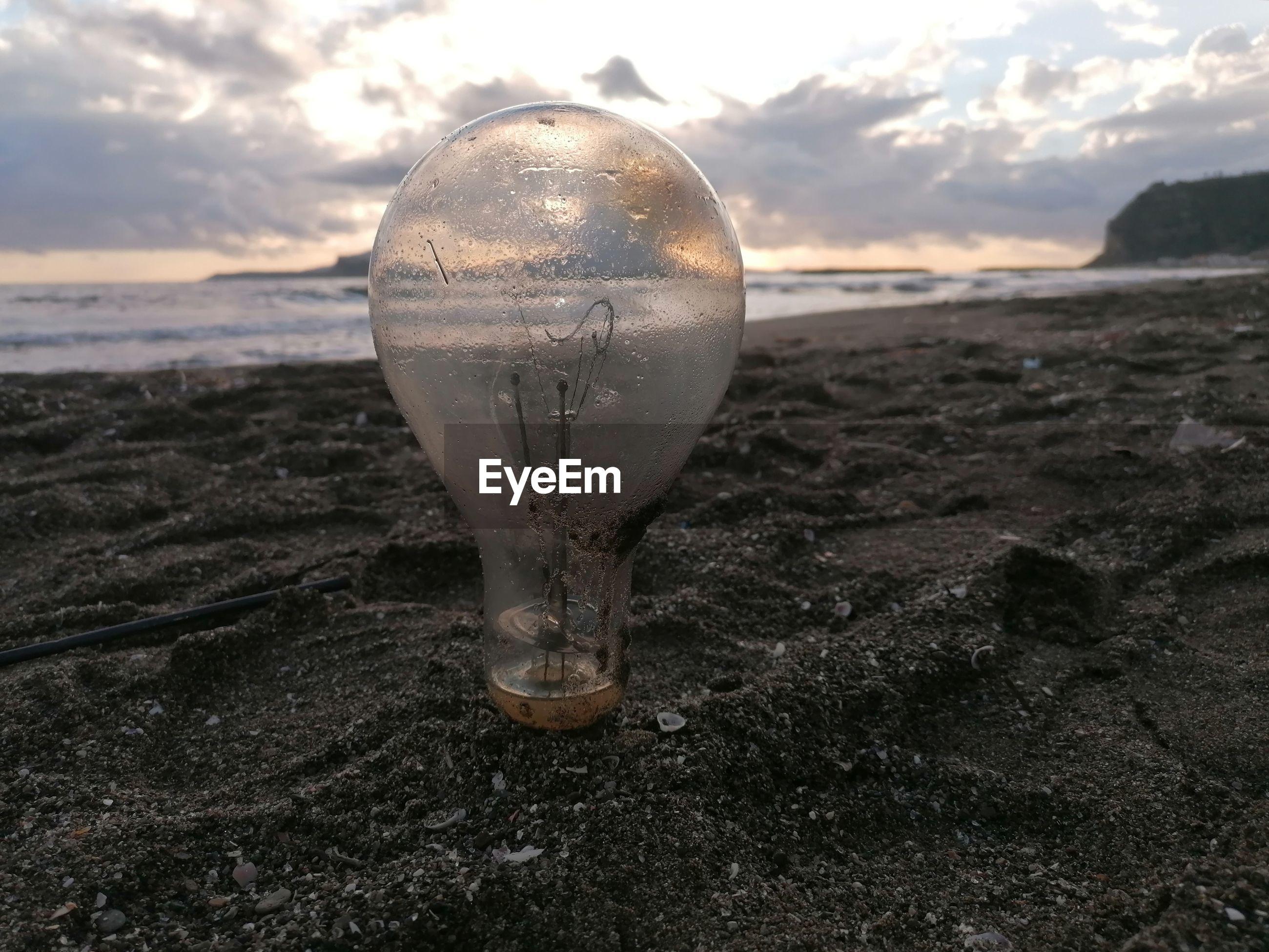 CLOSE-UP OF LIGHT BULB ON SAND
