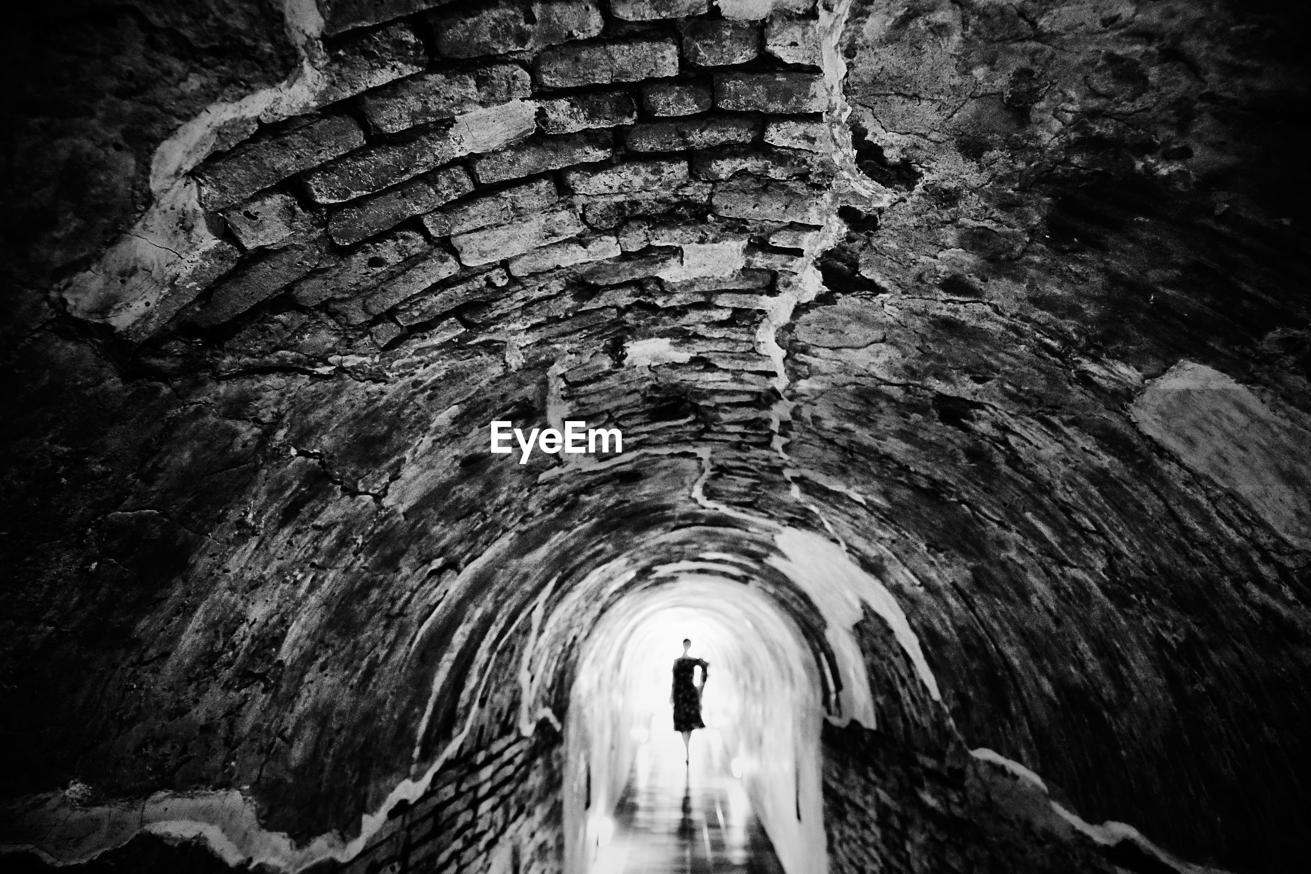 Mid distance view of woman standing in tunnel