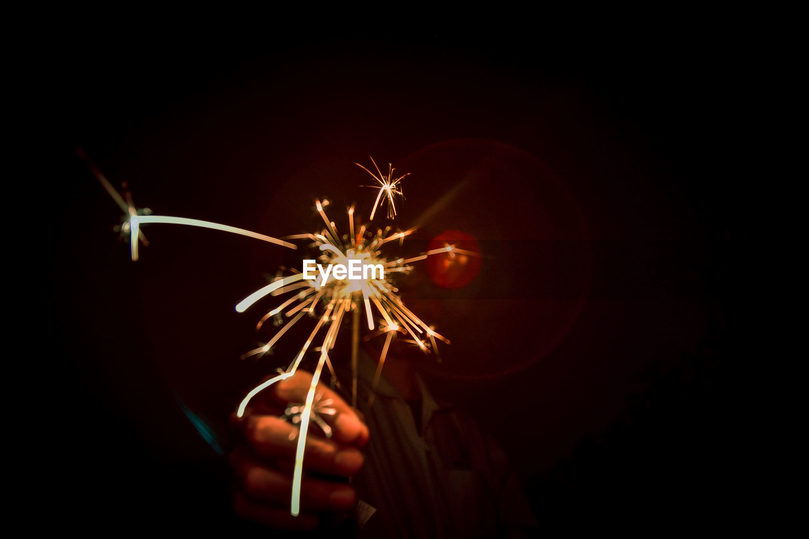 Person holding illuminated sparkler at night