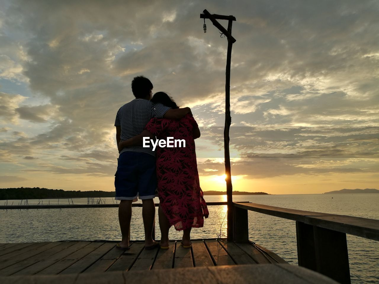 Rear view of couple standing by sea against sky during sunset