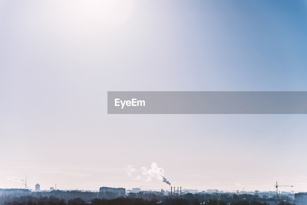 sky, smoke - physical structure, building exterior, factory, industry, smoke stack, emitting, no people, architecture, nature, copy space, pollution, built structure, environmental issues, air pollution, clear sky, environment, day, smoke, fumes, outdoors, atmospheric, ecosystem