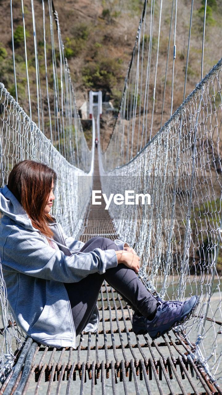 Side view of woman sitting on footbridge