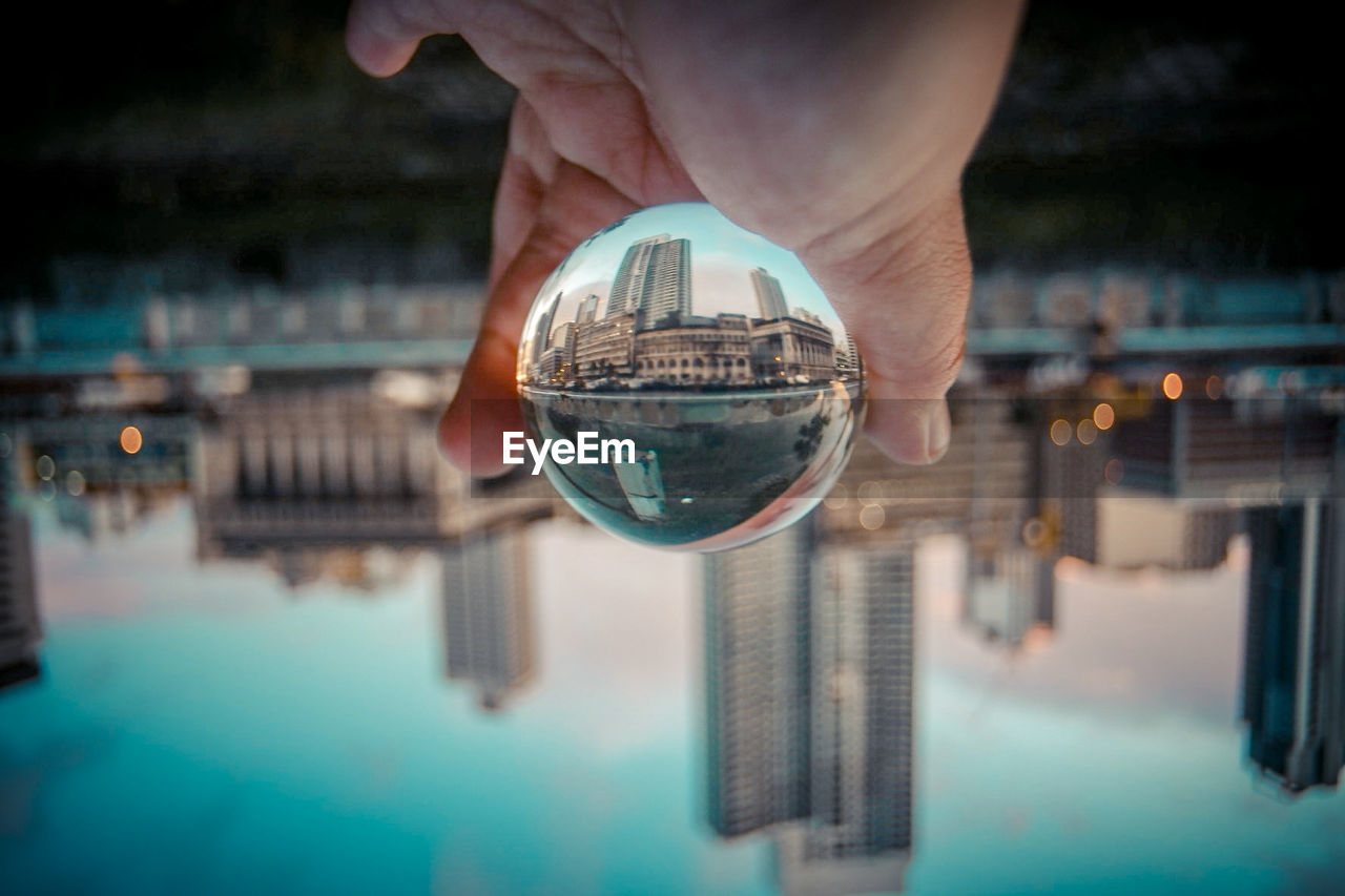 MIDSECTION OF PERSON HOLDING CRYSTAL BALL WITH REFLECTION OF WOMAN