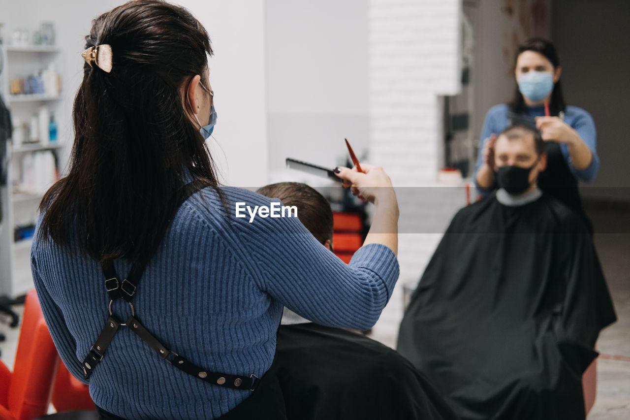 Barber shops, hair salons shutting down, second lockdown. hairdresser in face mask