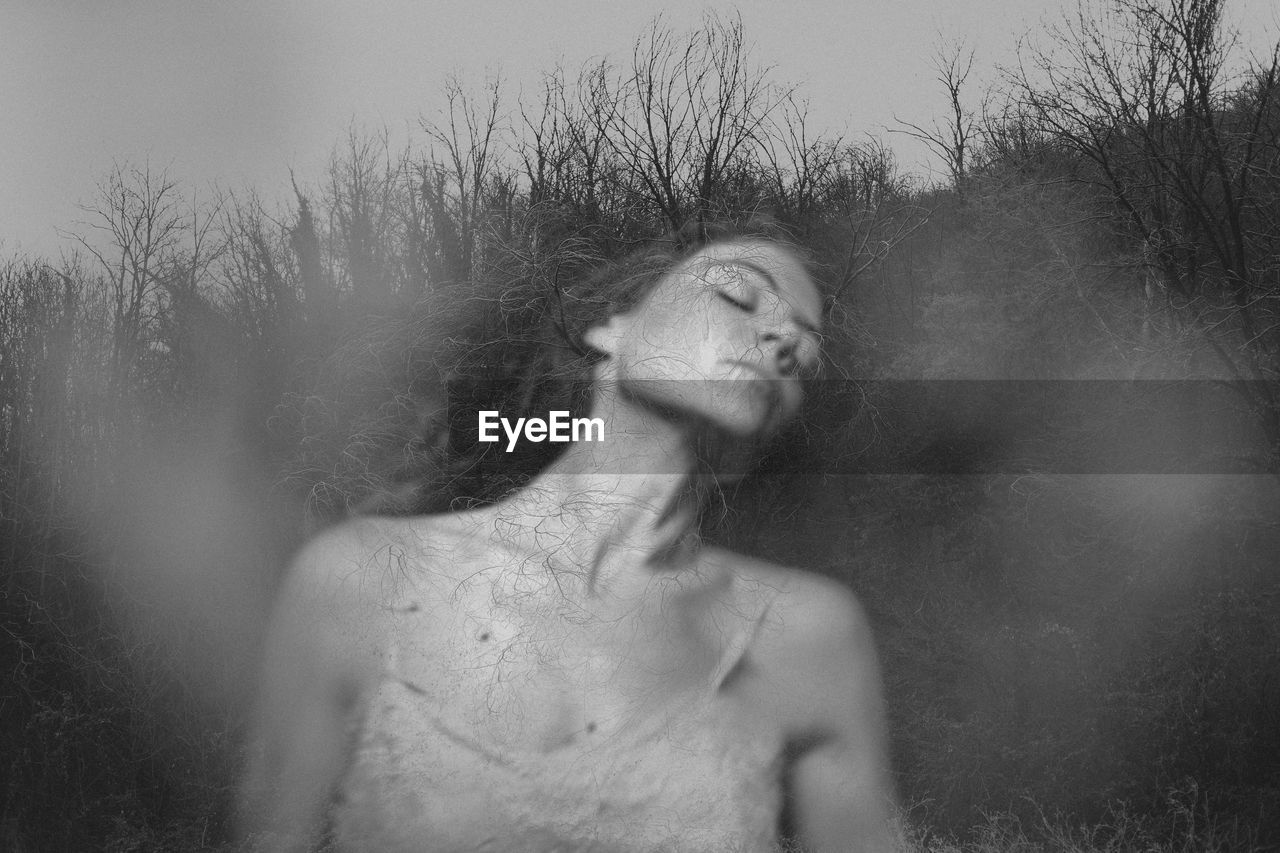 Double exposure of woman with eyes closed and bare trees