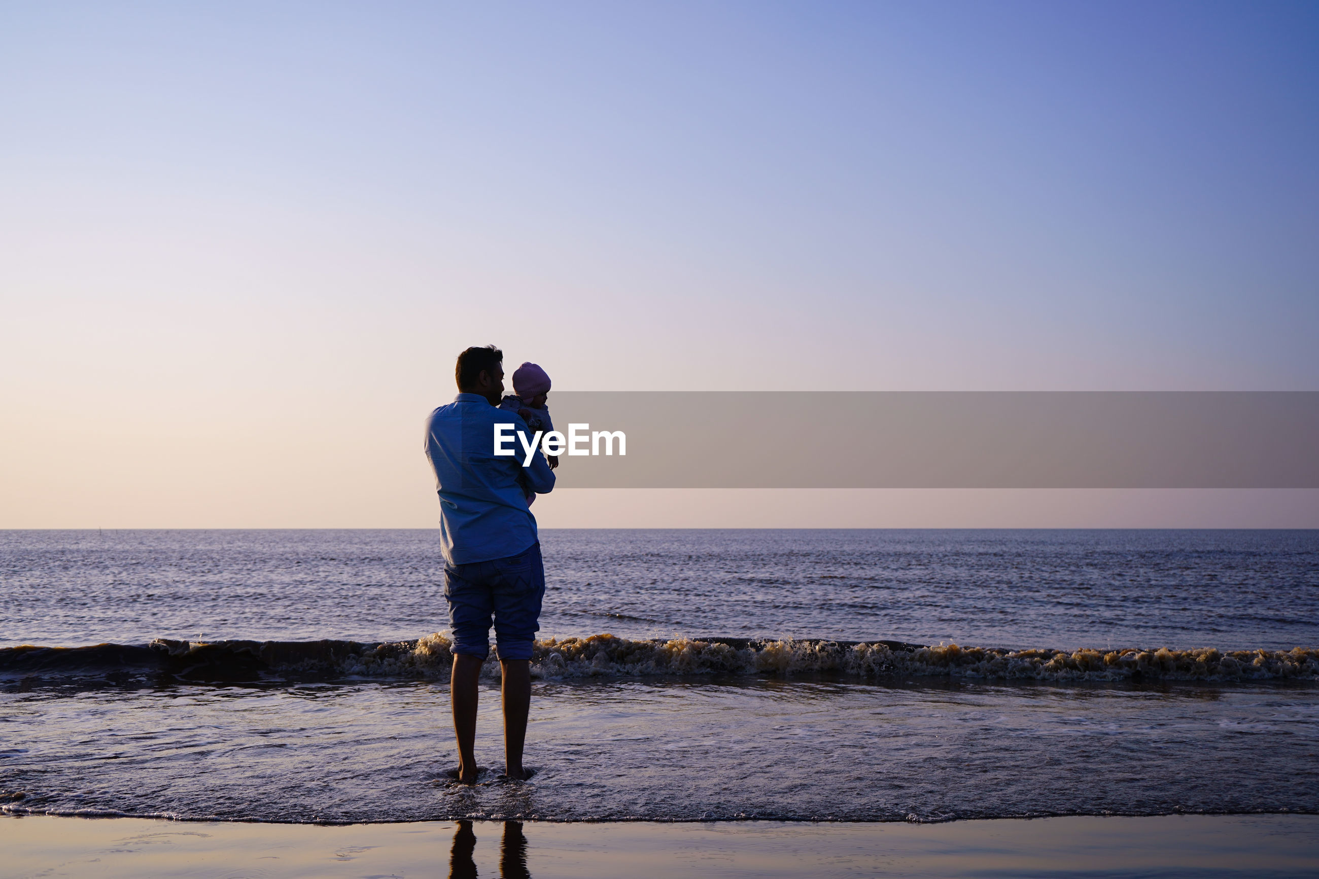 Rear view of man with toddler standing at beach against sky during sunset