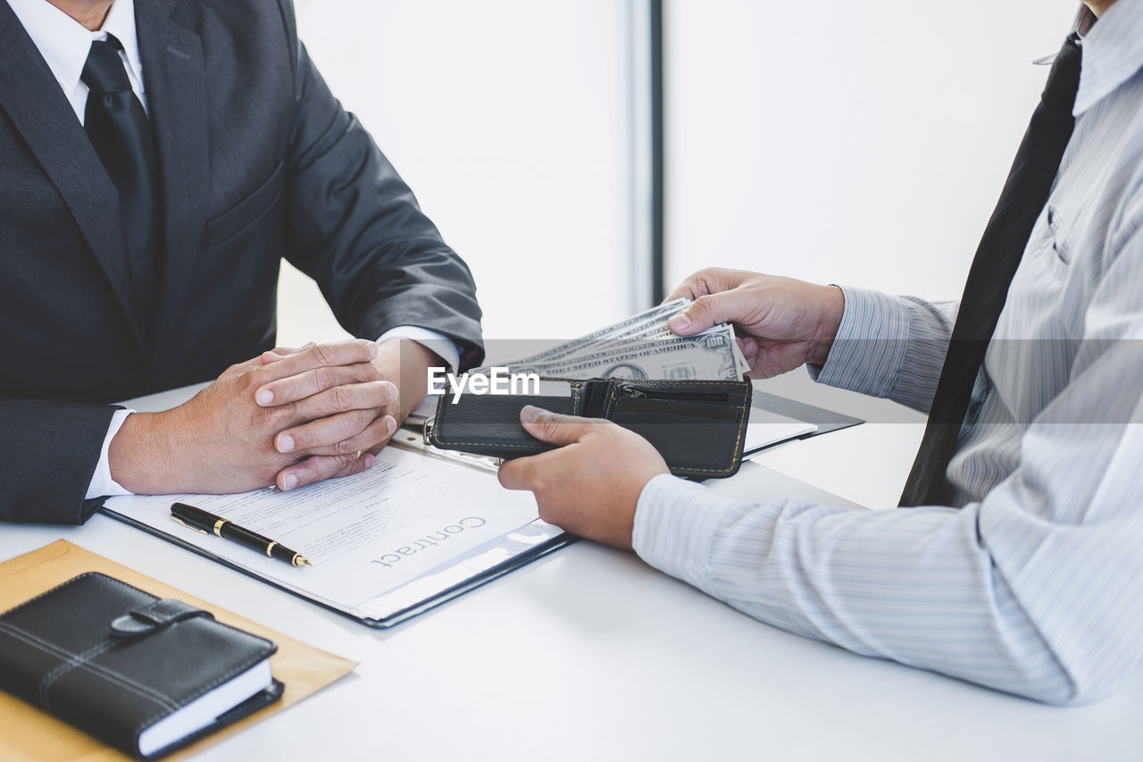 Midsection of businessman bribing manager at desk in office