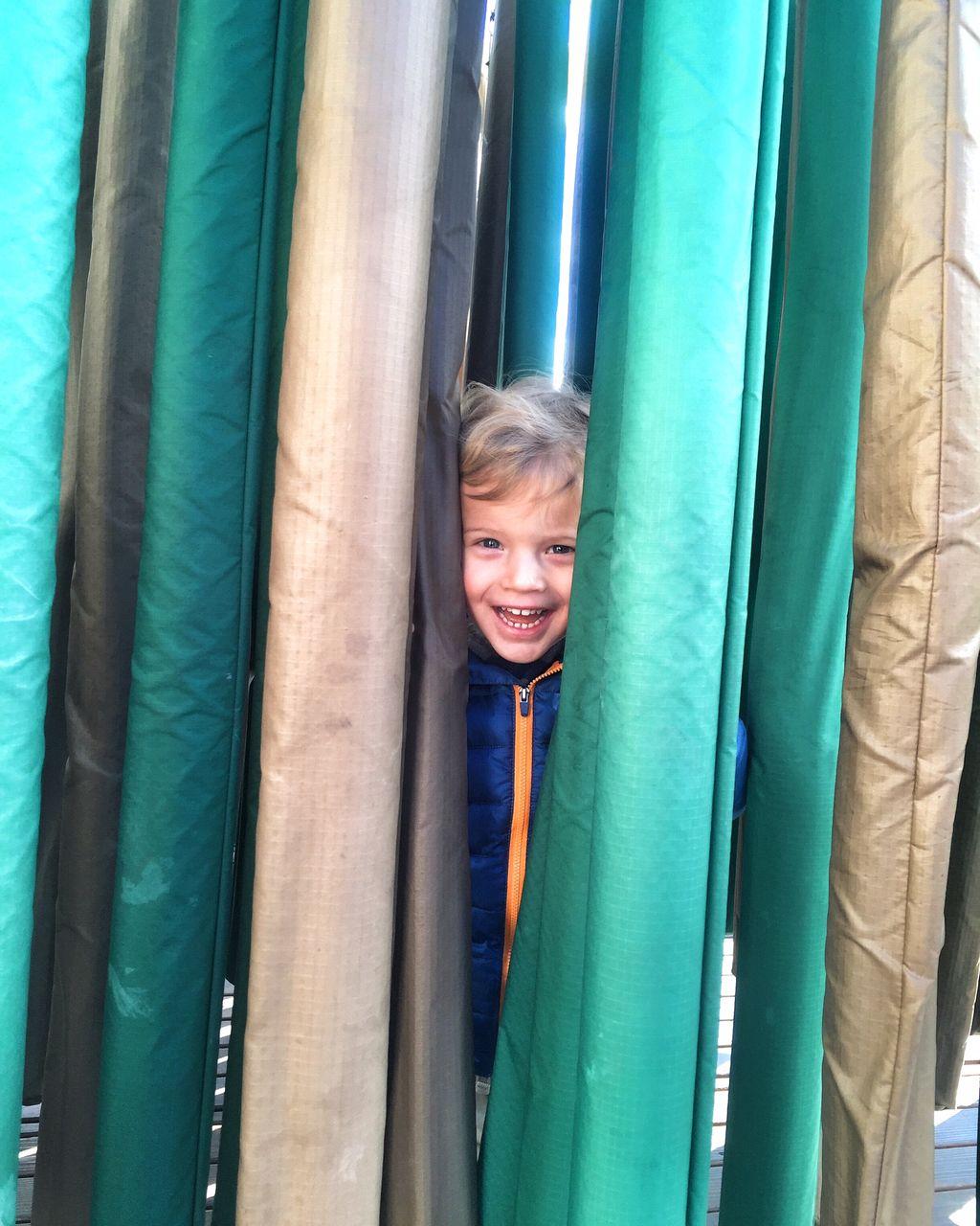 Portrait of happy boy peeking through fabrics