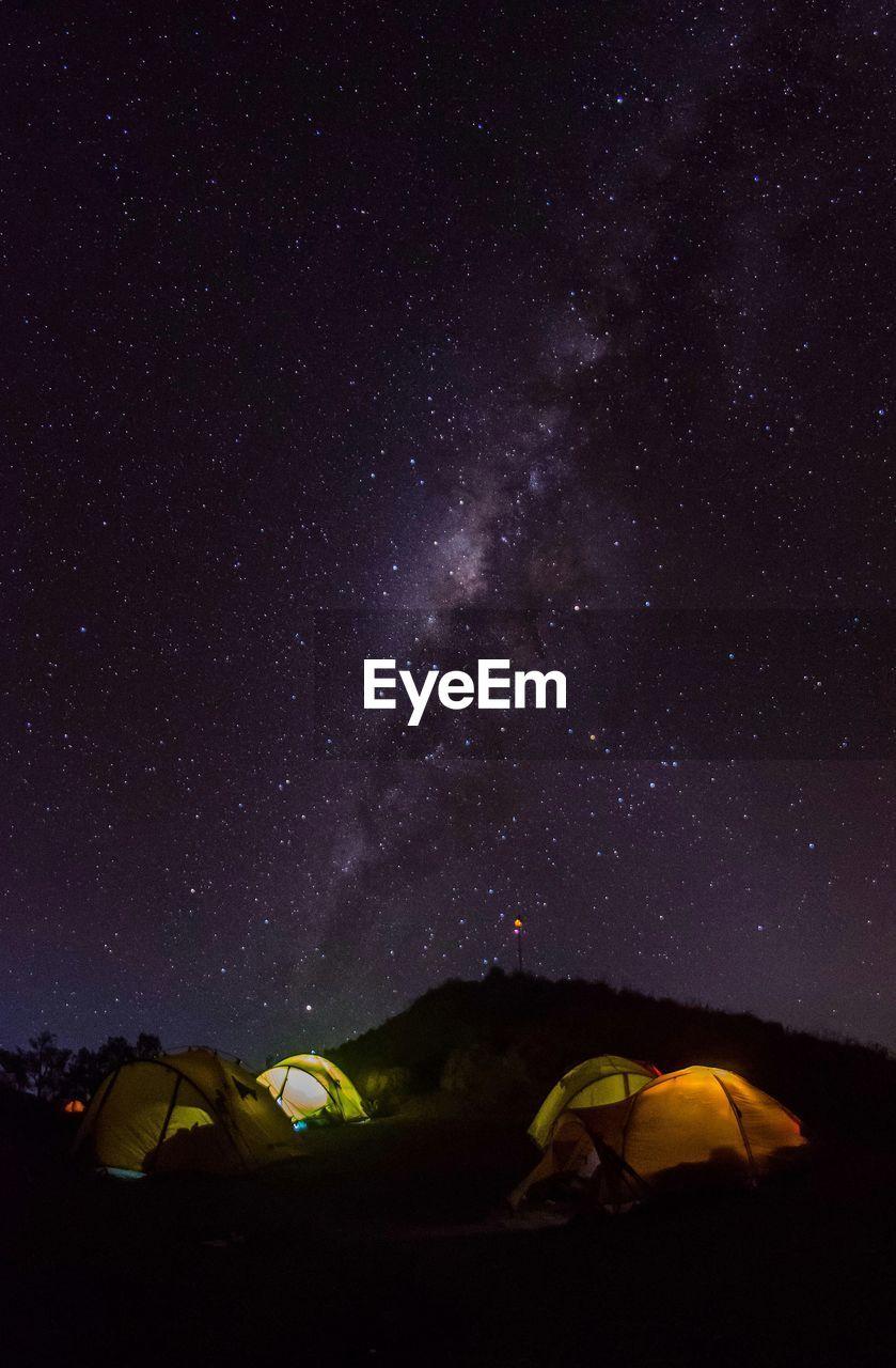Illuminated Tents On Field Against Sky At Night