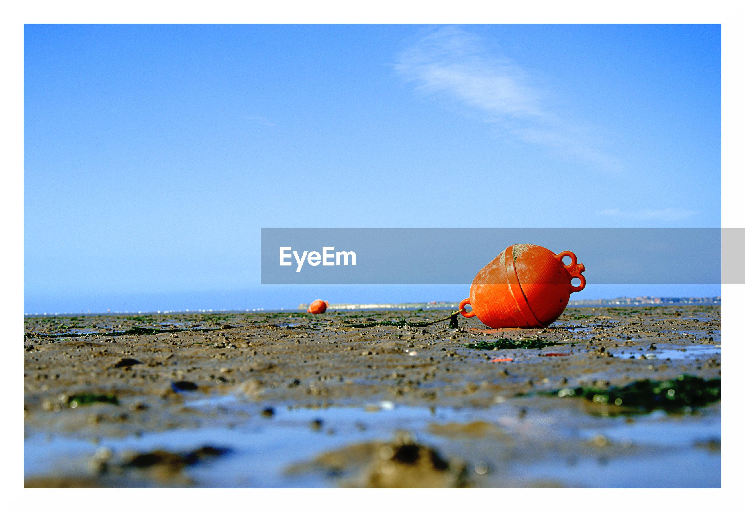Orange buoy on beach against sky