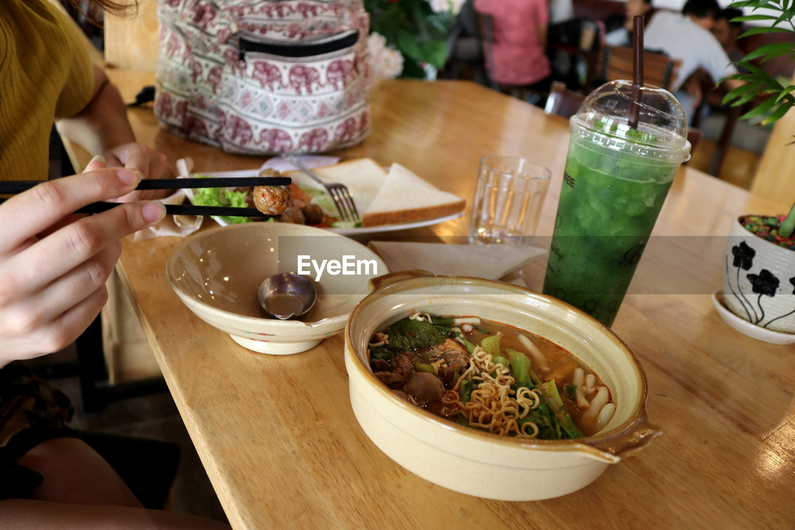 MIDSECTION OF WOMAN HAVING FOOD IN RESTAURANT