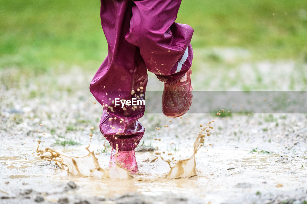 Low Section Of Child Playing In Puddle On Field