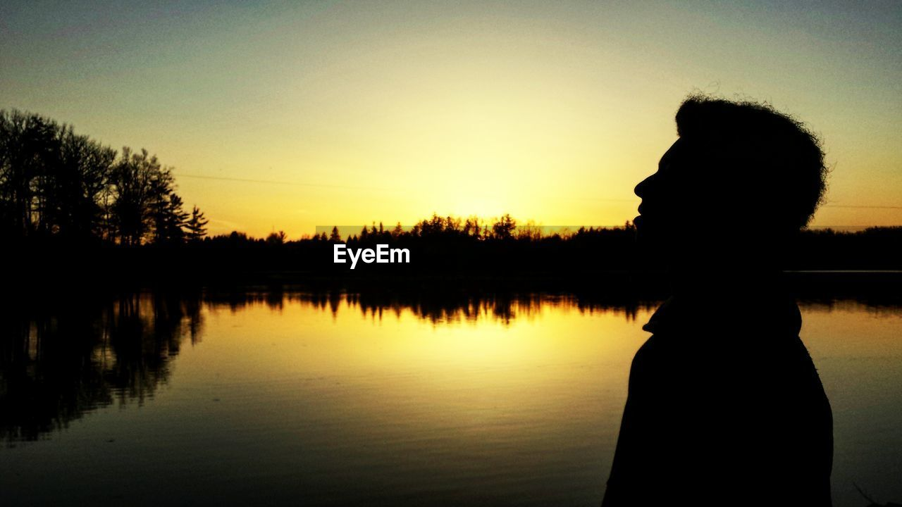 sunset, silhouette, reflection, real people, beauty in nature, water, nature, leisure activity, one person, lifestyles, tree, tranquil scene, scenics, lake, tranquility, women, outdoors, sky, side view, standing, vacations, growth, clear sky, people