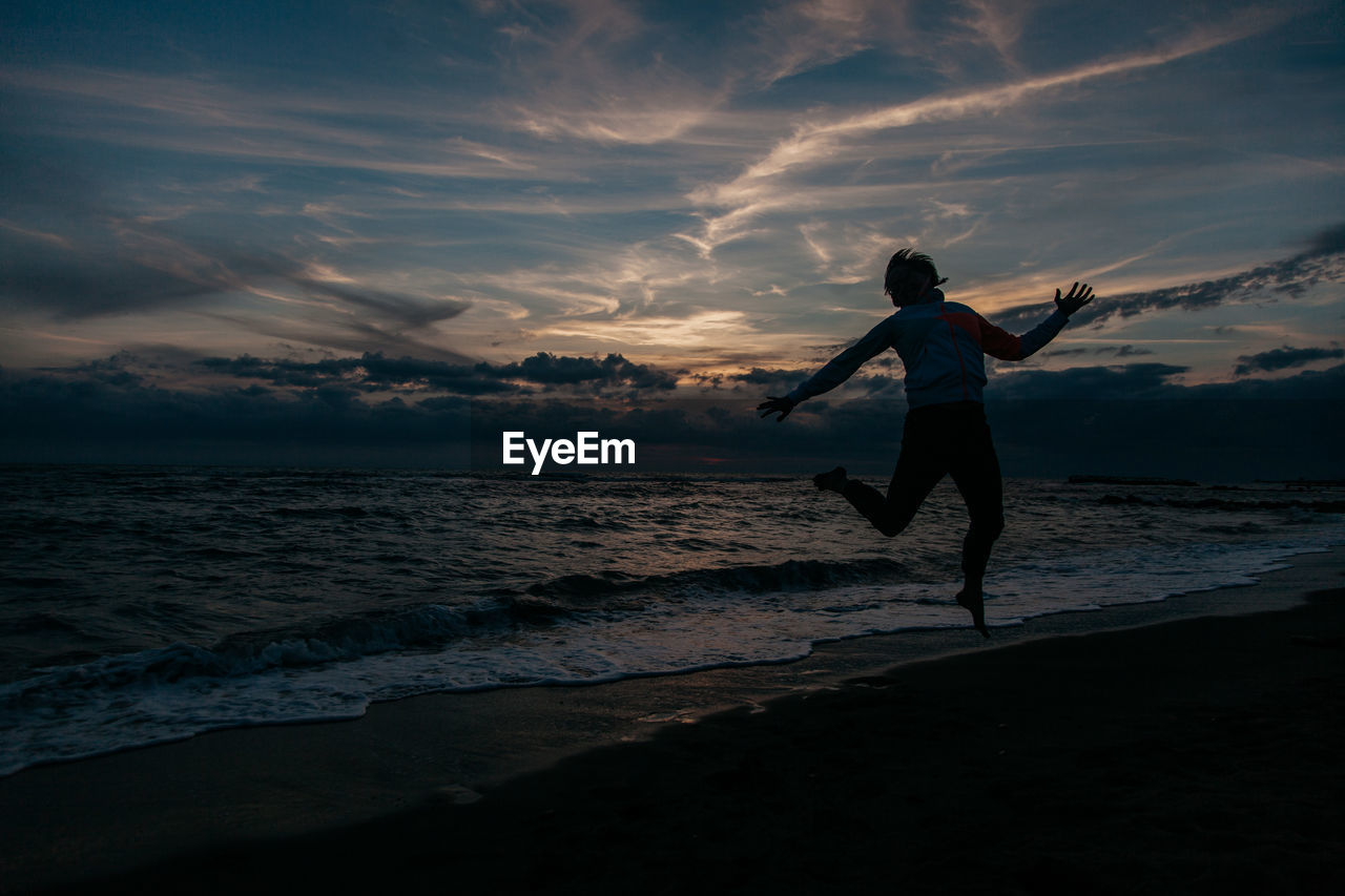 Silhouette woman jumping at beach against sky during sunset