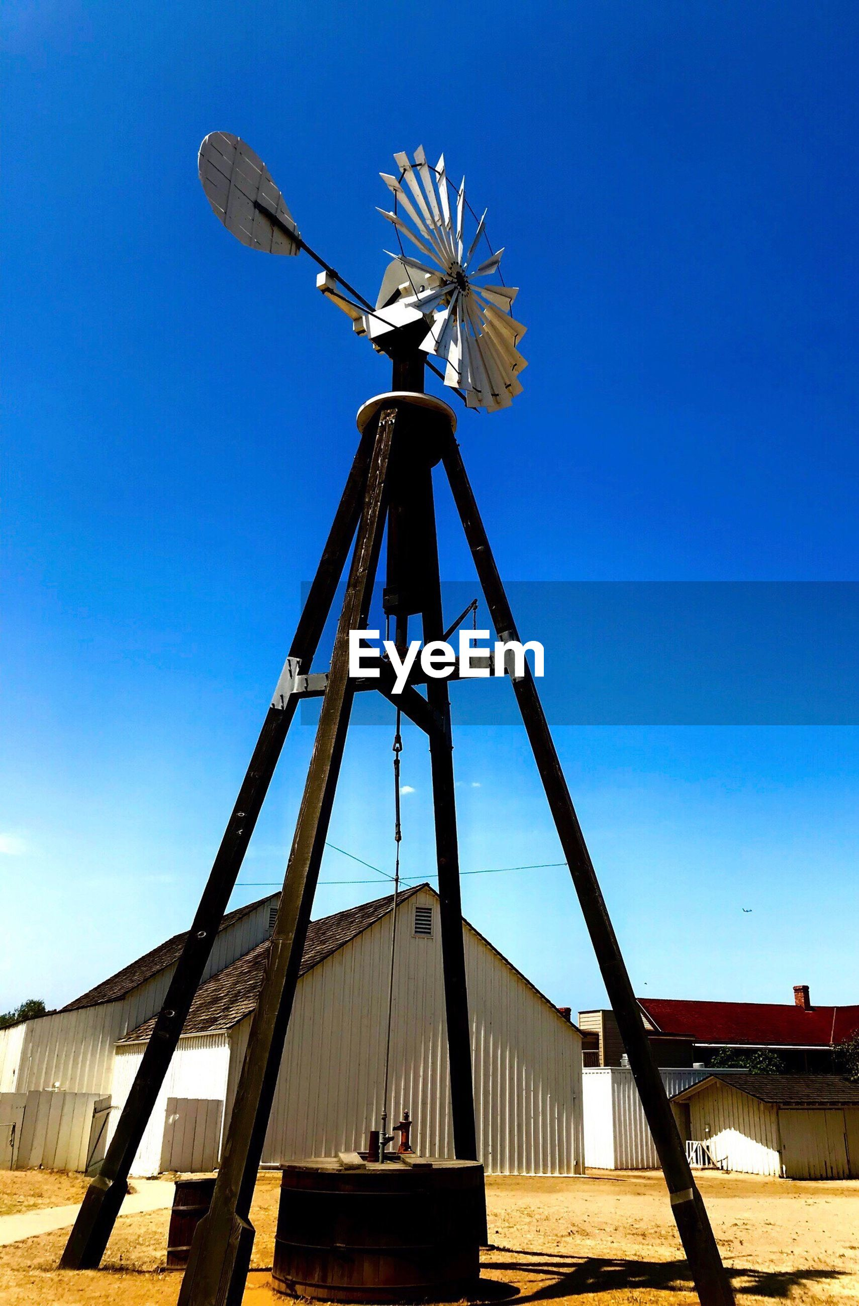 LOW ANGLE VIEW OF TRADITIONAL WINDMILL BY WINDMILLS AGAINST SKY