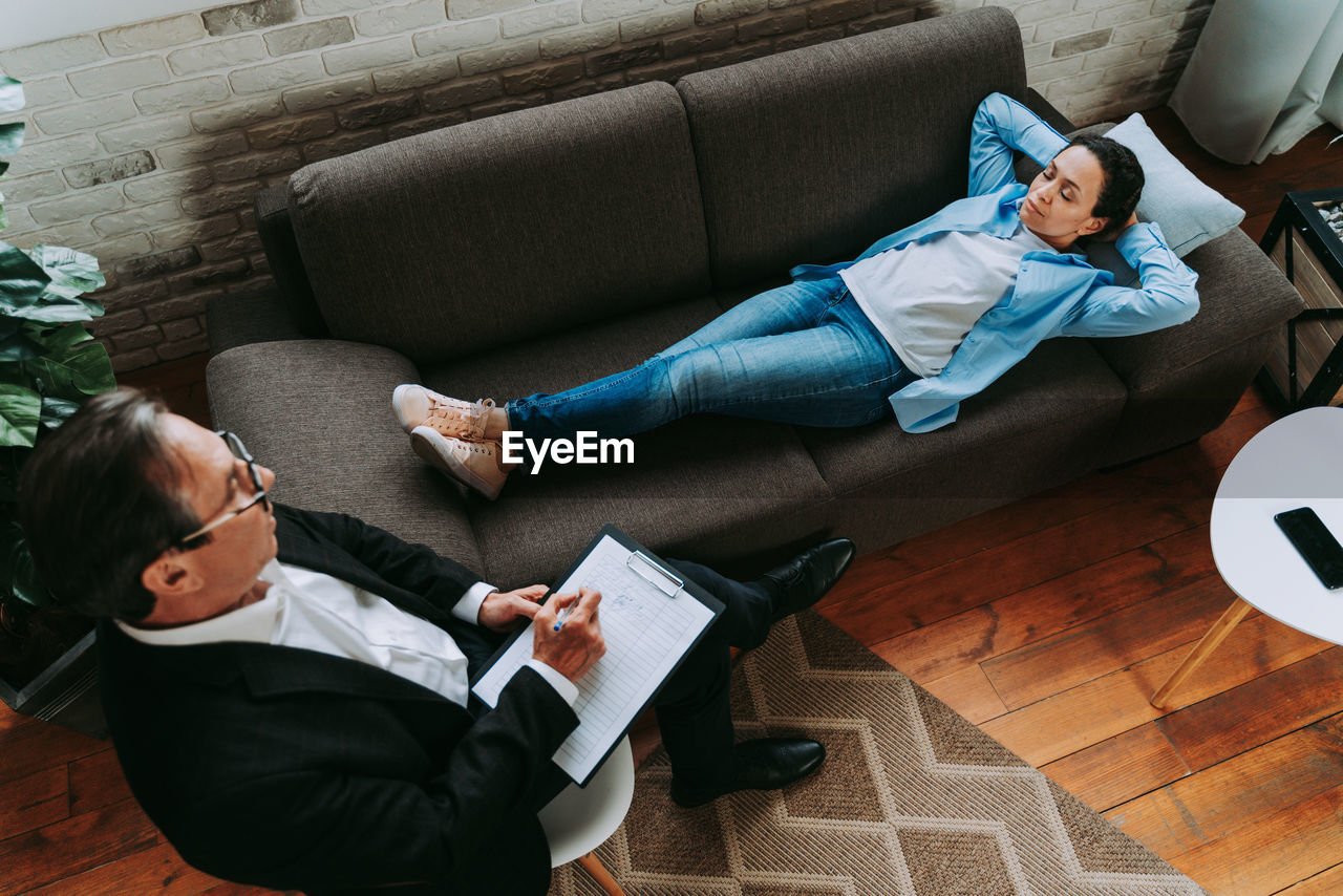 High angle view of men sitting on sofa at home