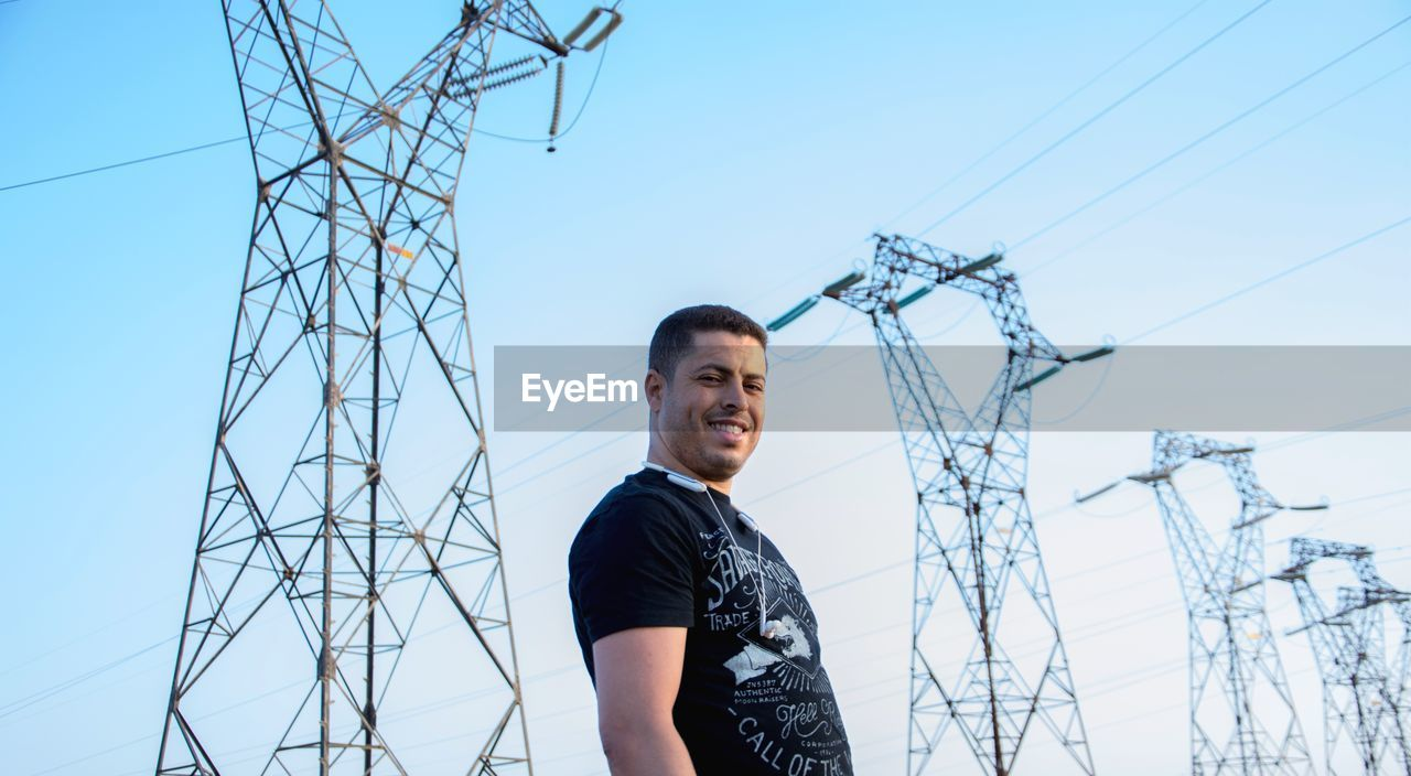 Portrait of man standing by electricity pylon against clear sky