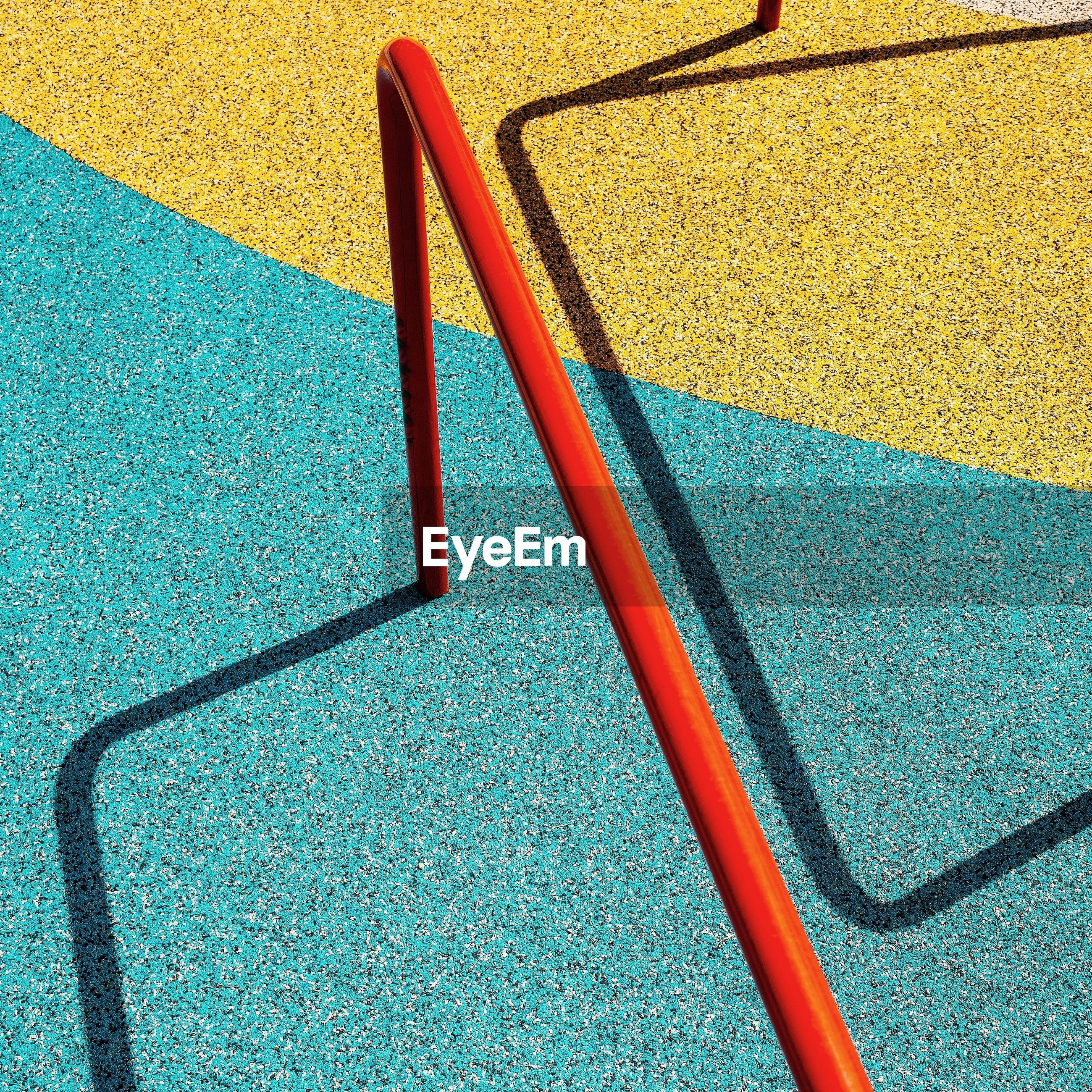 high angle view, no people, shadow, blue, multi colored, day, playground, sunlight, close-up, still life, yellow, indoors, flooring, nature, pattern, design, green color, outdoor play equipment, single line