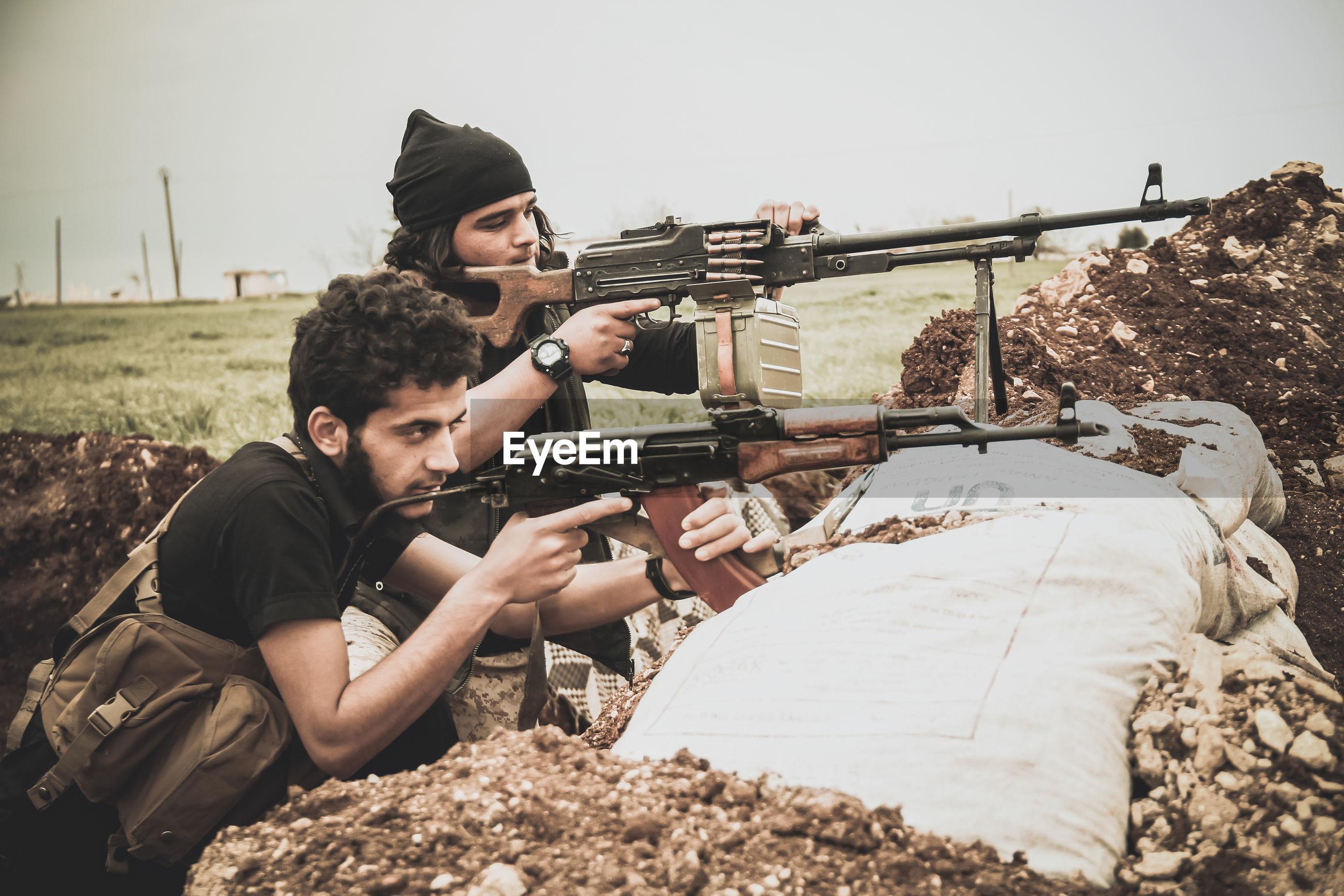 Terrorist holding rifles against sky
