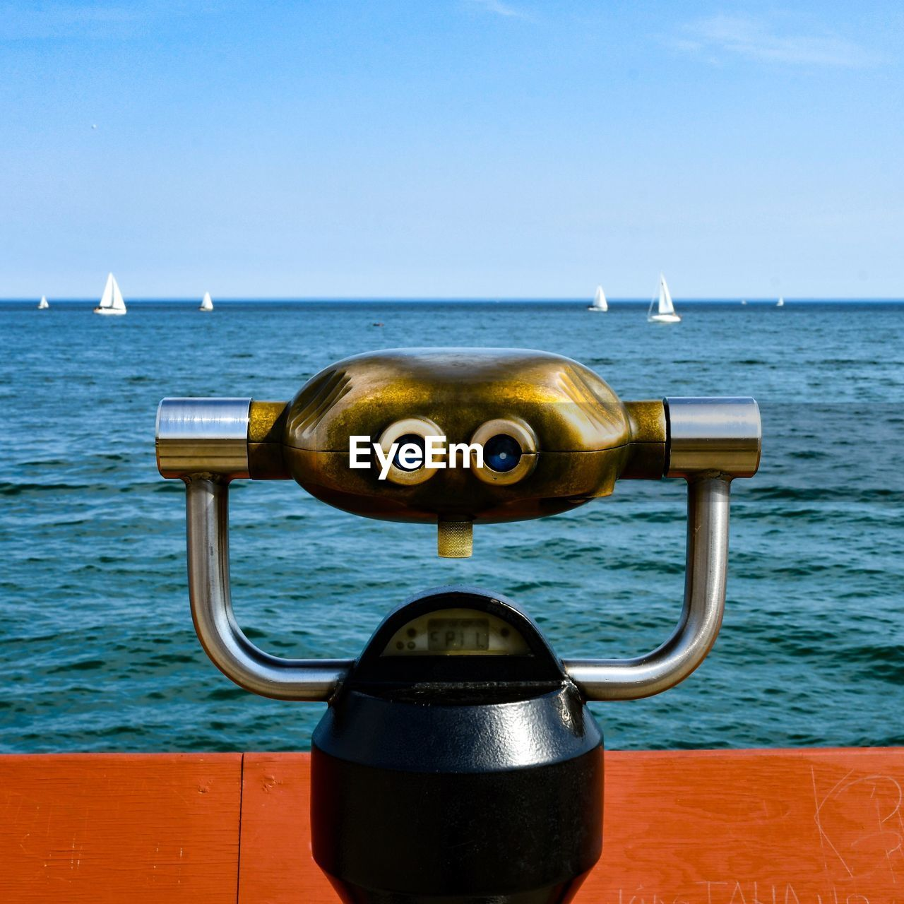 CLOSE-UP OF COIN-OPERATED BINOCULARS AGAINST SEA AGAINST SKY