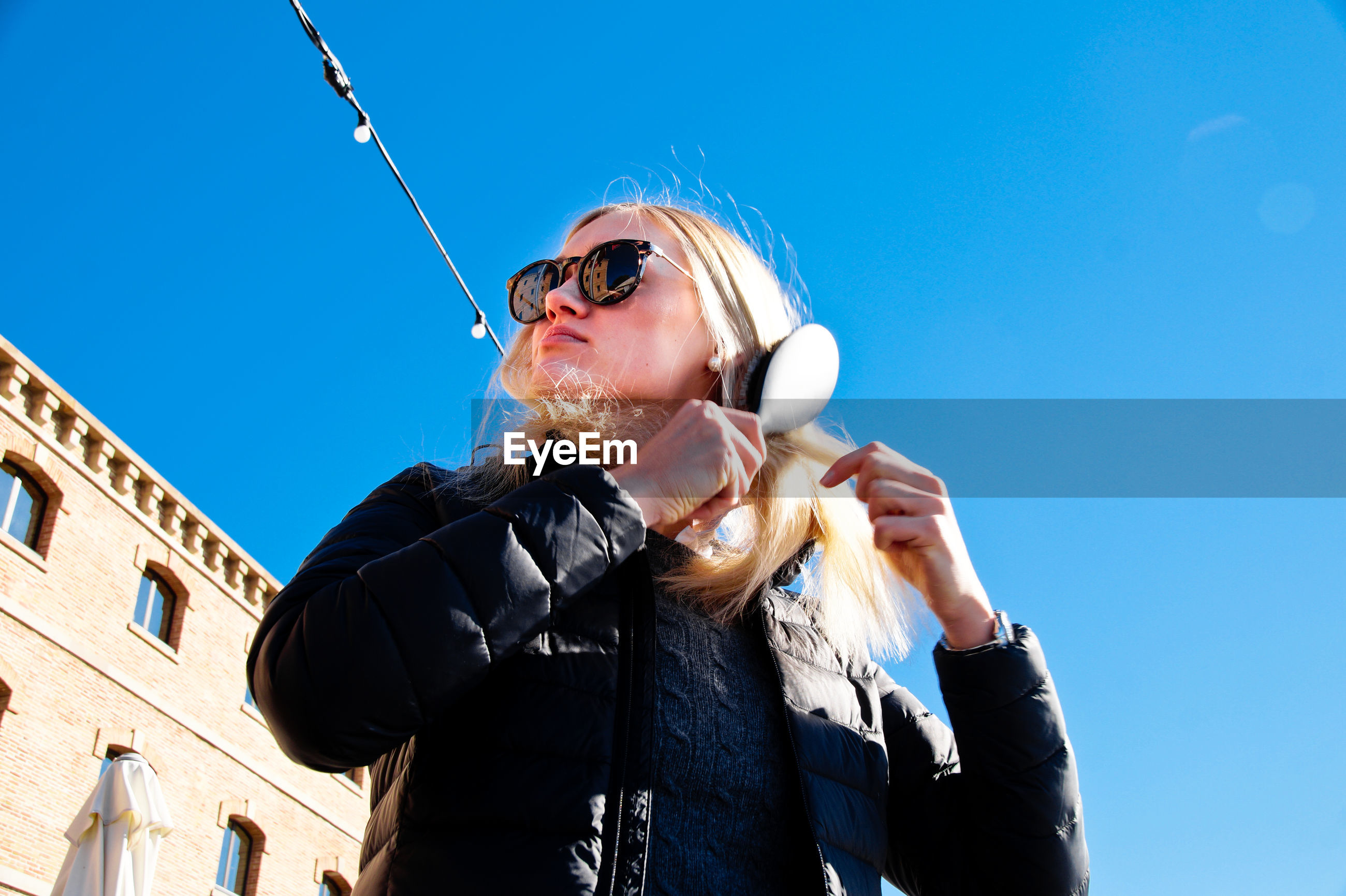 Low angle view of woman combing hair against clear sky