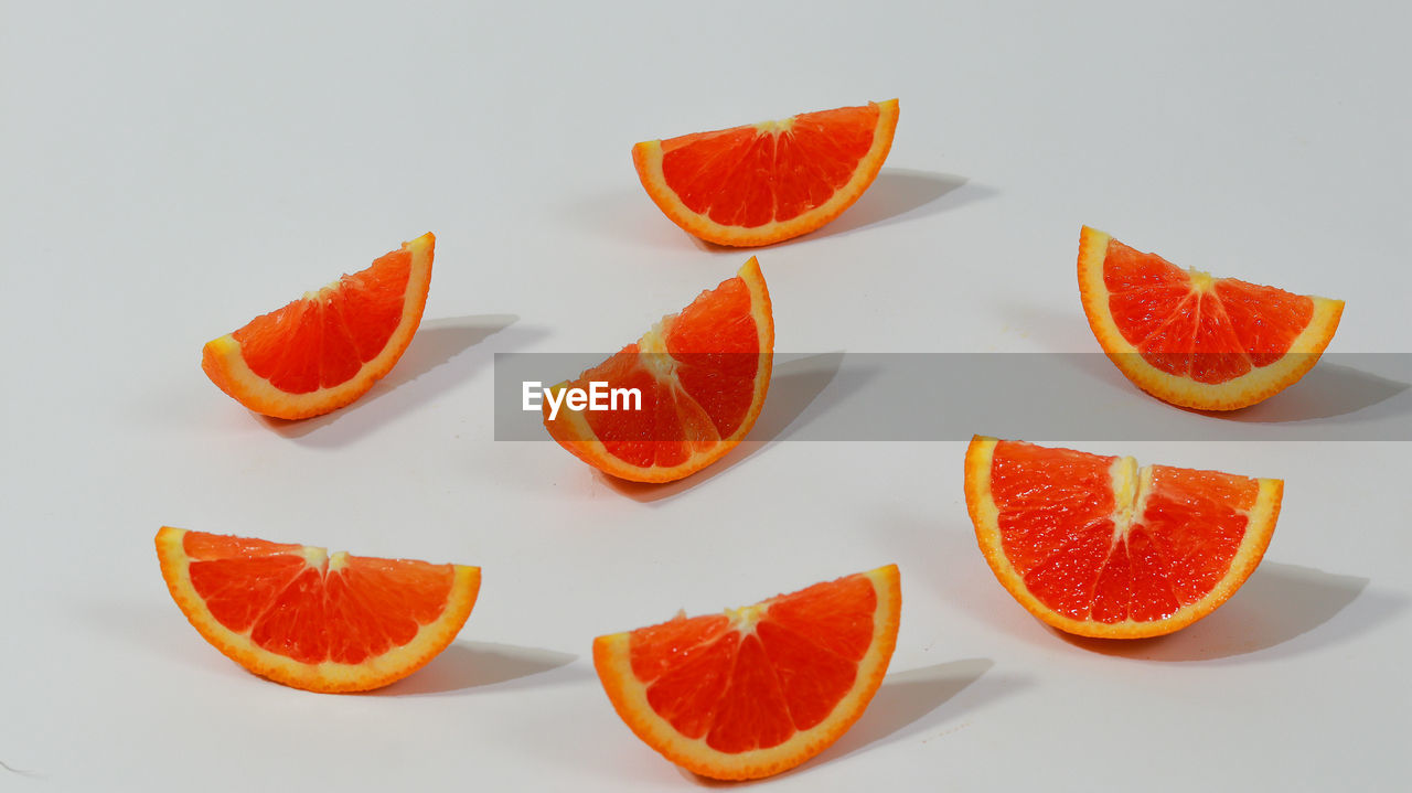 orange color, citrus fruit, food and drink, food, slice, orange, fruit, orange - fruit, healthy eating, wellbeing, freshness, indoors, no people, cross section, studio shot, still life, white background, group of objects, table, close-up, ripe