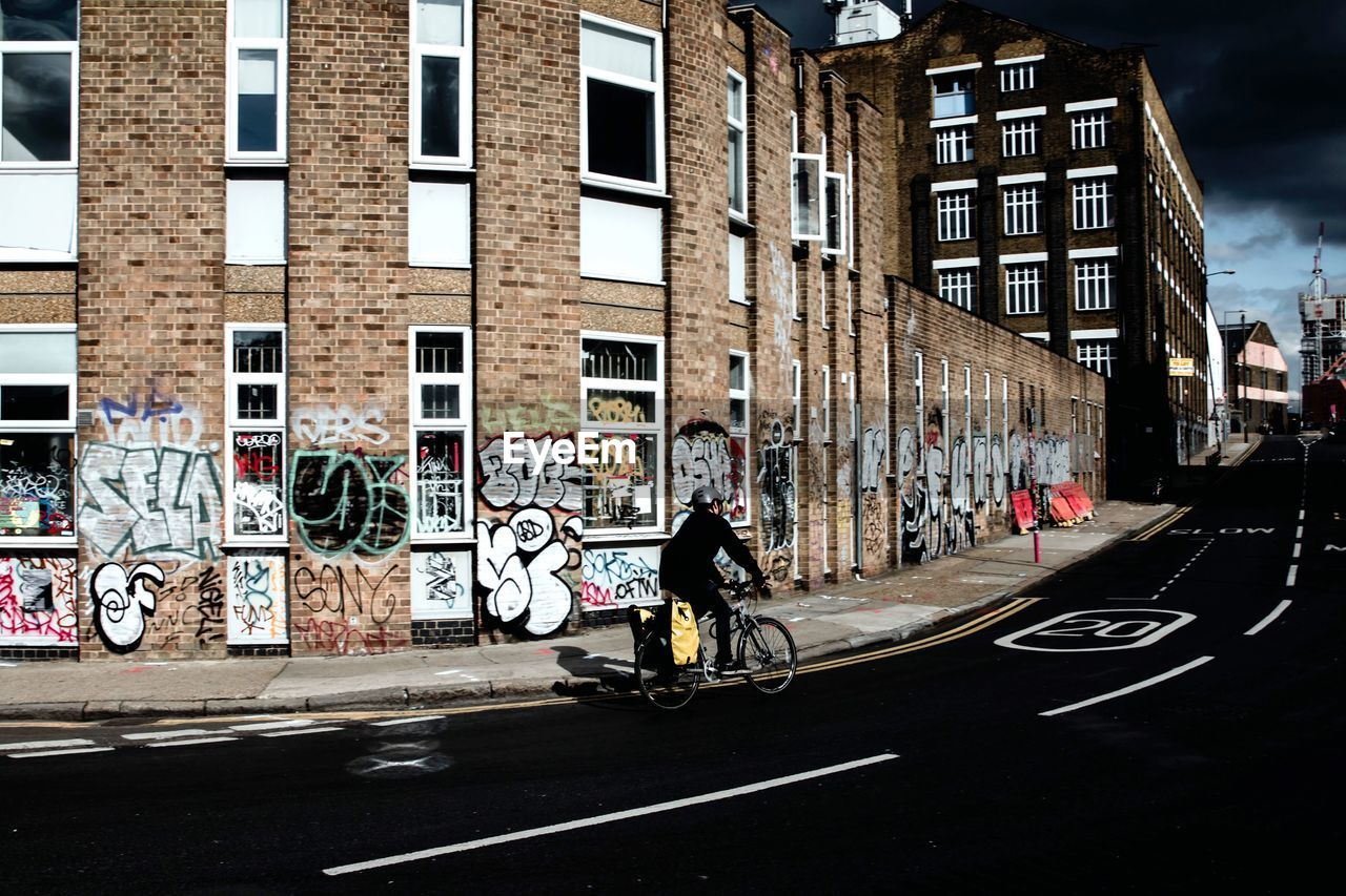 architecture, building exterior, built structure, graffiti, real people, city, transportation, bicycle, one person, outdoors, day, full length, road, motorcycle, biker, men, sky, adult, people