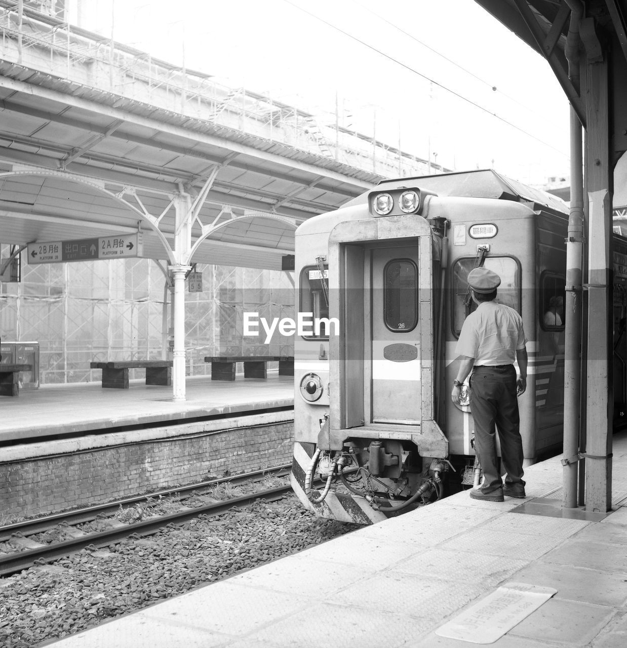 Rear View Of Train Conductor Standing By Train At Railroad Station Platform