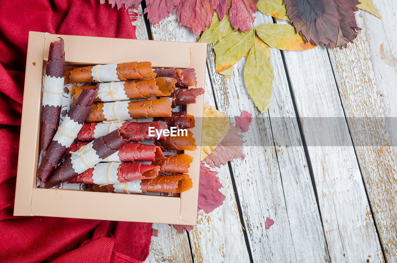 wood - material, food and drink, food, freshness, high angle view, table, day, meat, directly above, one person, human body part, holding, still life, outdoors, healthy eating, human hand, real people, barbecue, close-up, ready-to-eat, snack