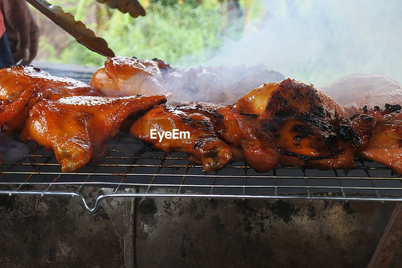 food, meat, food and drink, barbecue, freshness, no people, smoke - physical structure, heat - temperature, close-up, metal, grilled, chicken meat, ready-to-eat, day, outdoors, high angle view, barbecue grill, chicken, still life, preparing food, white meat, snack, temptation