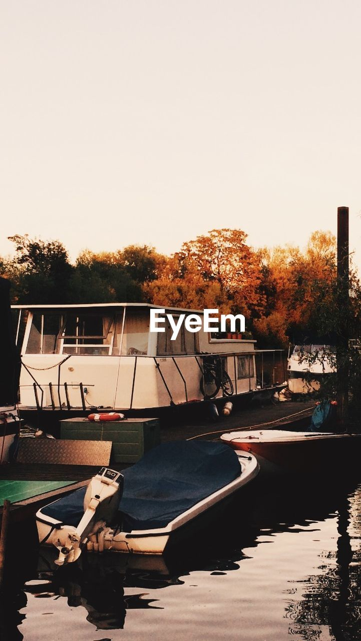 nautical vessel, tree, no people, water, clear sky, transportation, river, moored, outdoors, day, nature, autumn, built structure, architecture, sky