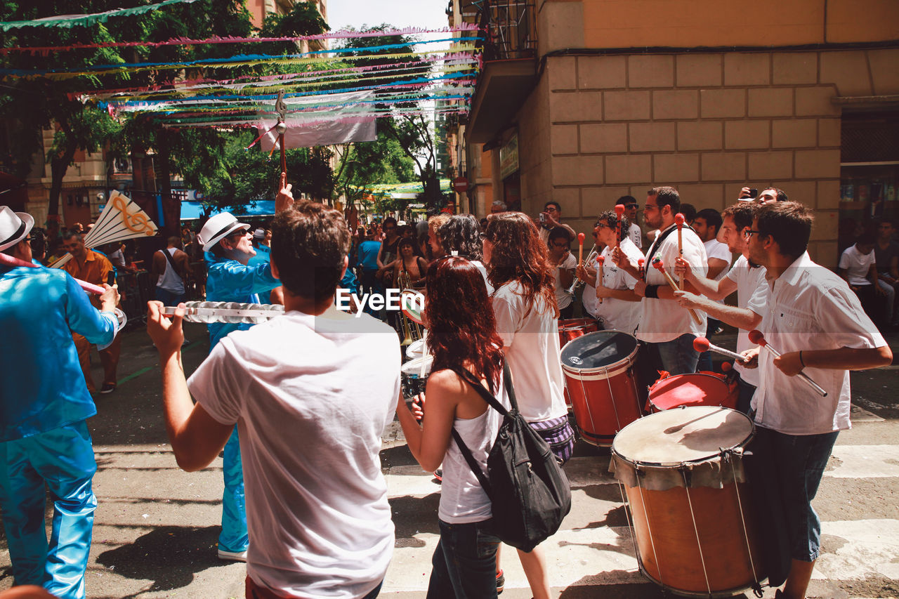 real people, large group of people, music, musician, men, outdoors, drum - percussion instrument, musical instrument, togetherness, drum, day, traditional festival, arts culture and entertainment, women, building exterior, standing, performance, crowd, architecture, people