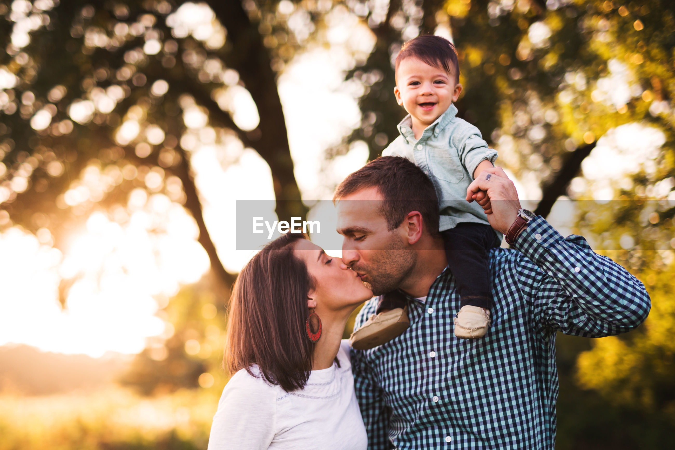 Portrait of cute smiling baby boy while parents kissing in park