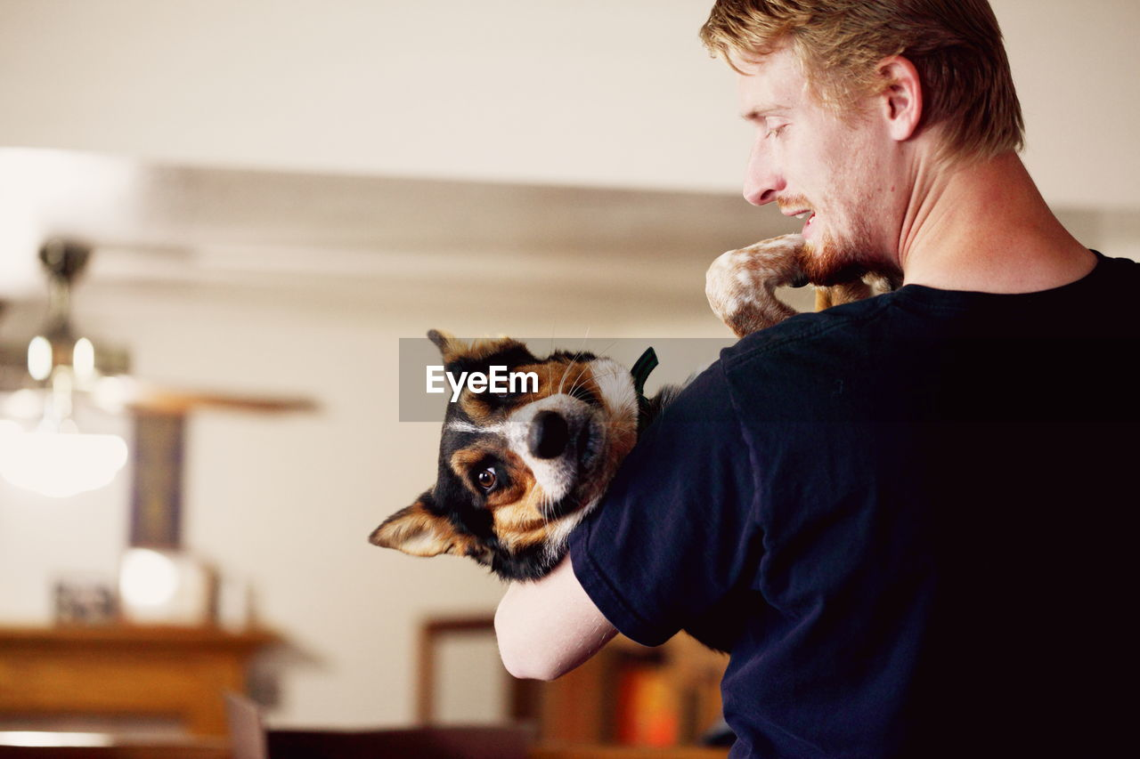 Rear View Of Young Man Carrying Dog While Standing At Home