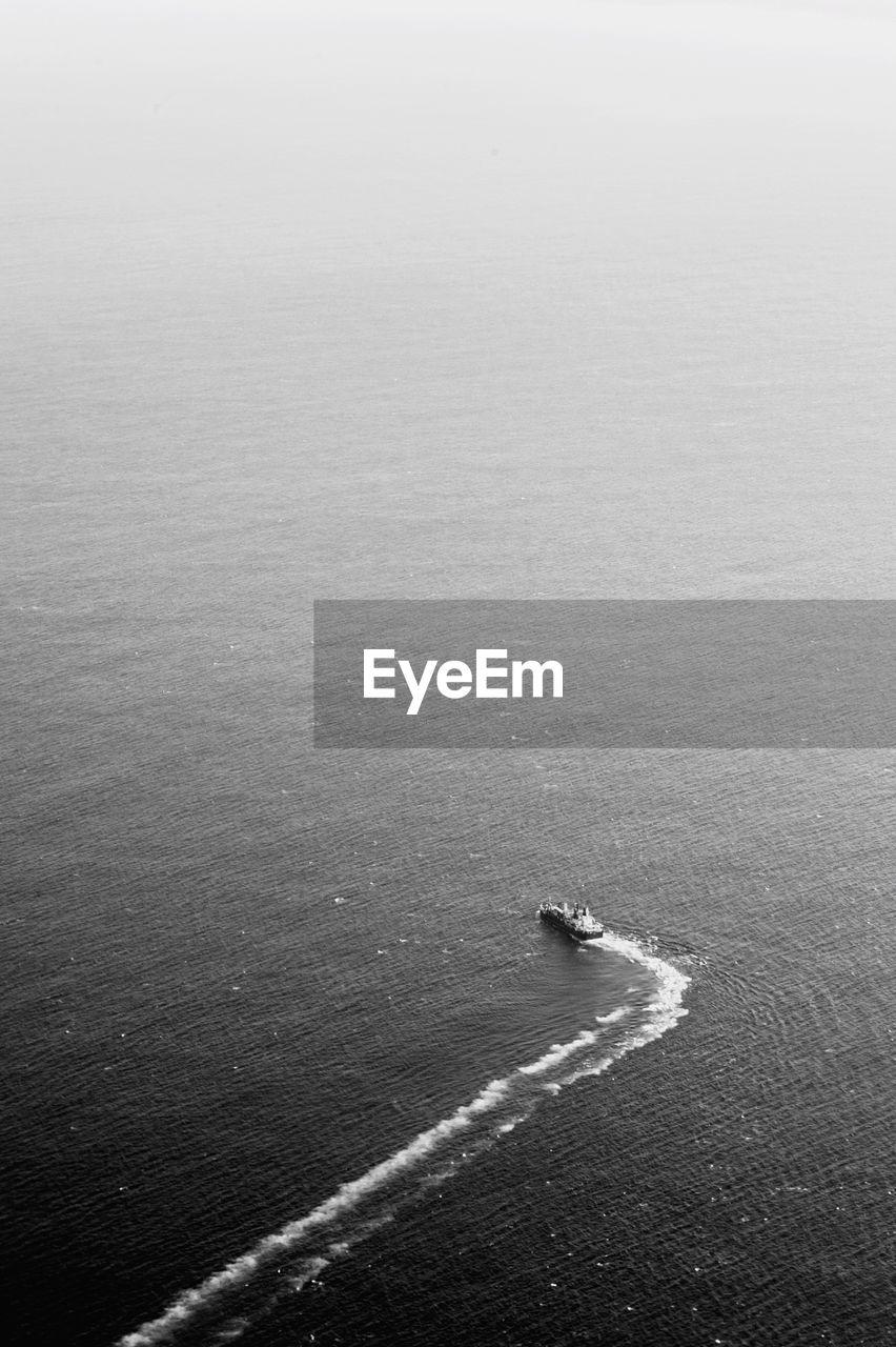 HIGH ANGLE VIEW OF MAN SAILING ON SEA