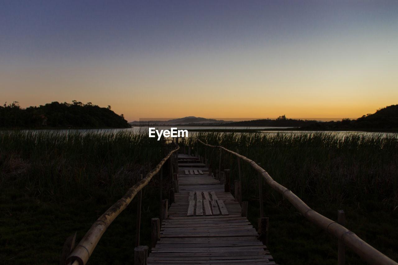 Walkway By Lake During Sunset