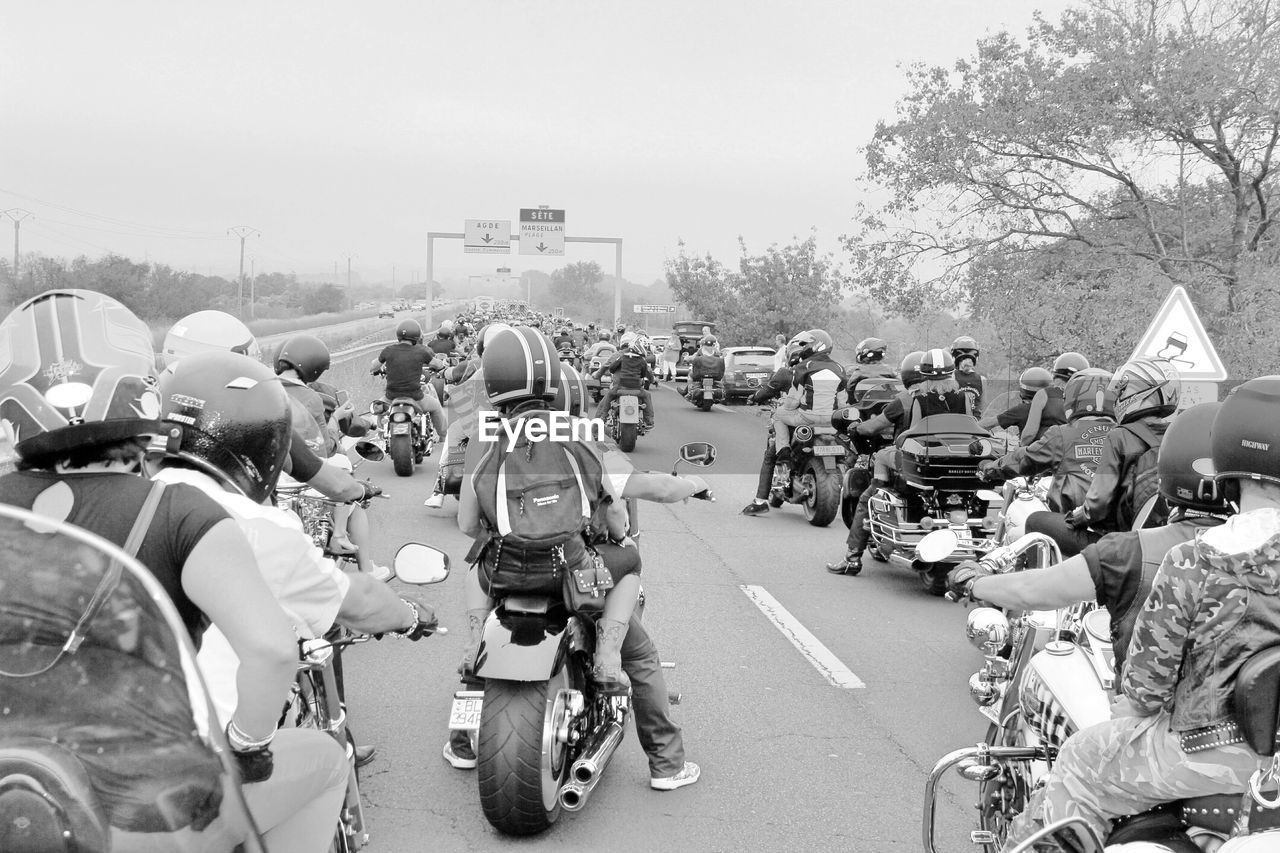 transportation, street, motorcycle, road, land vehicle, real people, large group of people, mode of transport, city, outdoors, bicycle, men, tree, building exterior, built structure, day, women, architecture, helmet, scooter, sky, clear sky, biker, adult, people