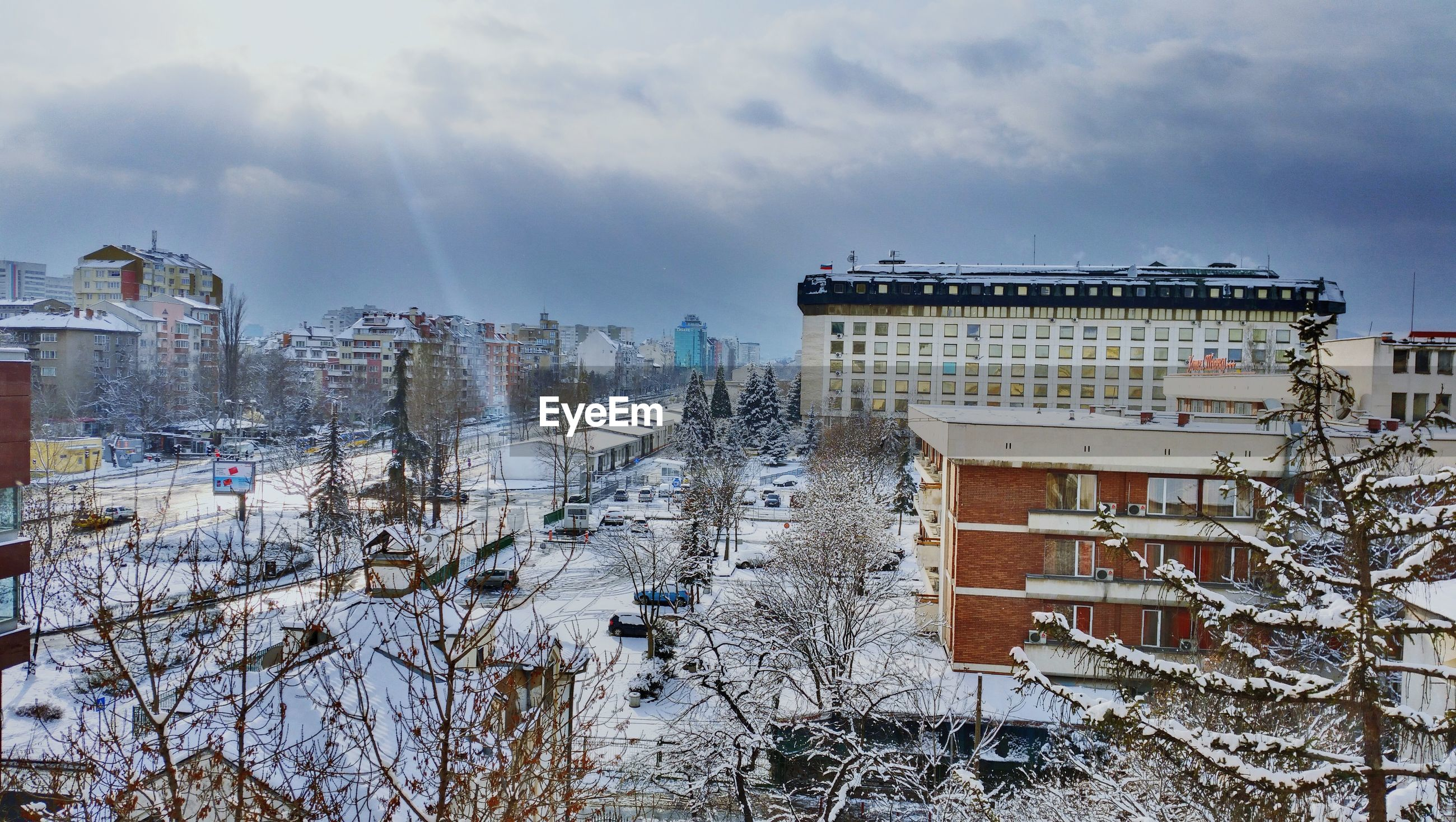 High angle view of street and buildings during winter against cloudy sky